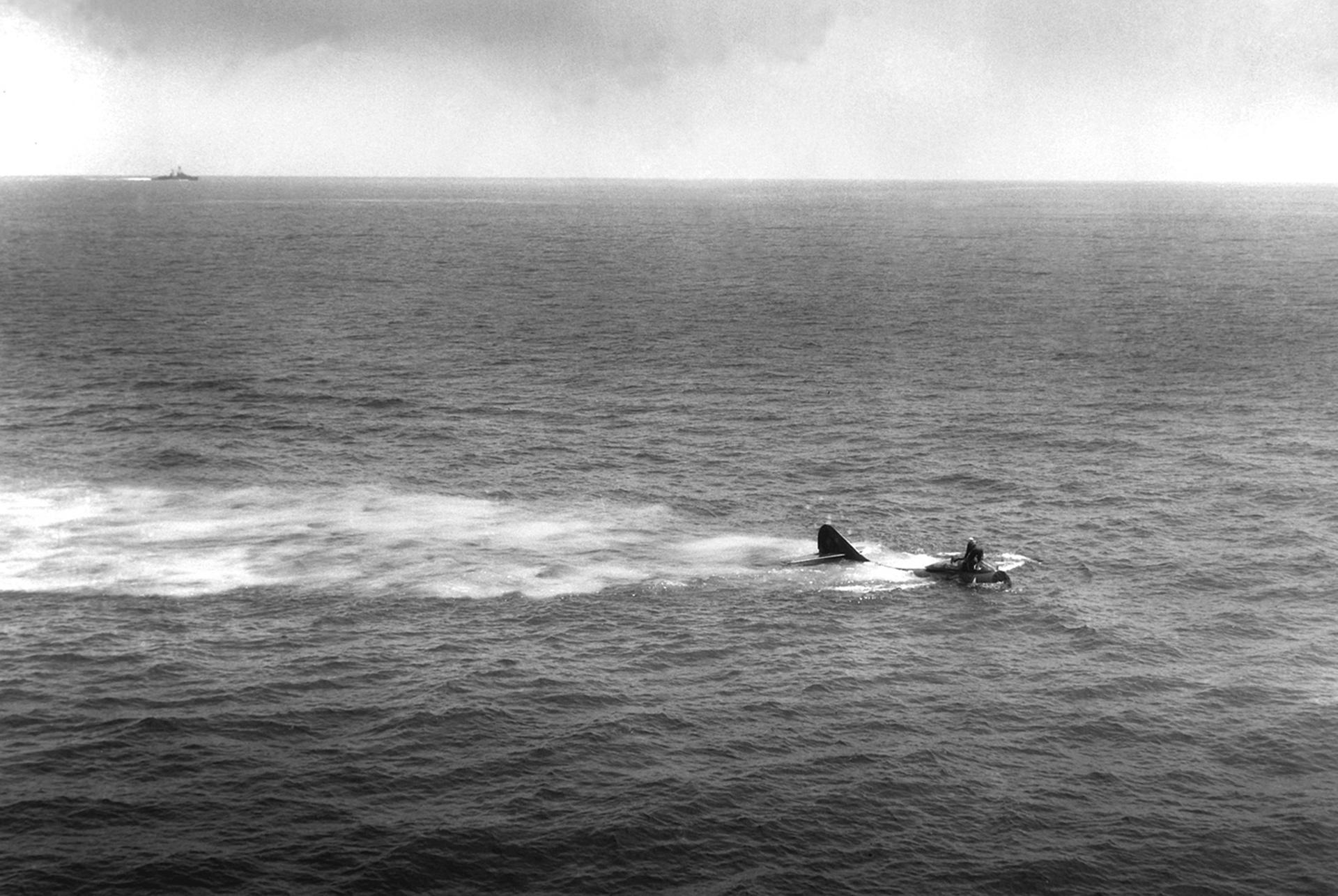 Un avión F9F-2 flotando en el mar después de un accidente, mientras un buque va a su rescate (US Department of Defense)