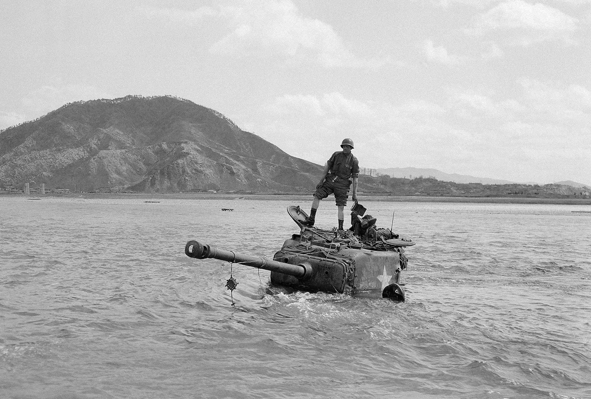 Miembros de la tripulación en la parte superior de su tanque después de quedarse varados durante una inmersión en el río Pukhan. El tanque fue remolcado a un lugar seguro el 7 de abril de 1951 en Corea (AP)