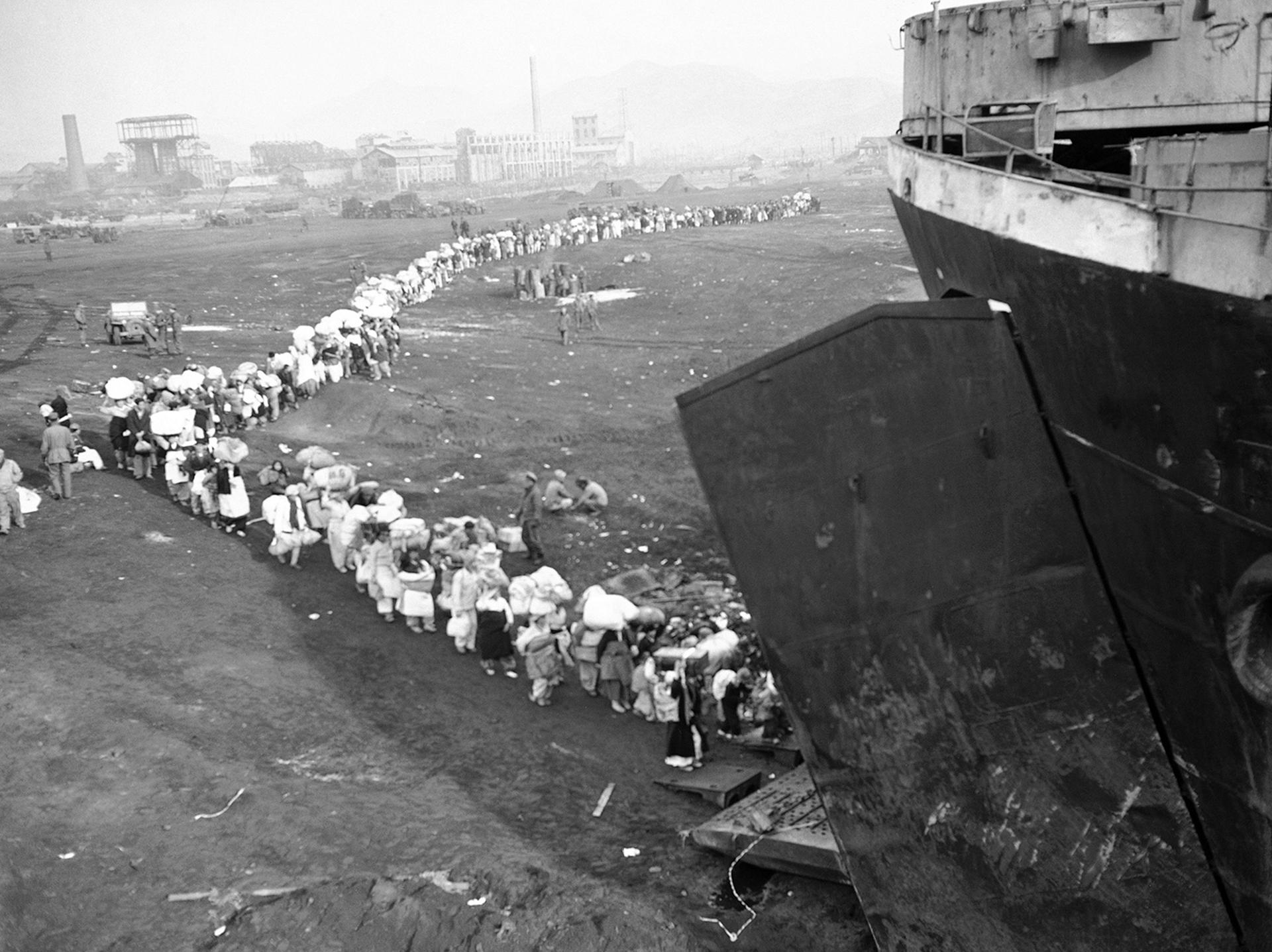 Una larga fila de refugiados de Corea, abordan un buque en el puerto de Hungnam, Corea del Norte el 21 de diciembre de 1950, escapando de los avances de los comunistas chinos y norcoreanos (AP)