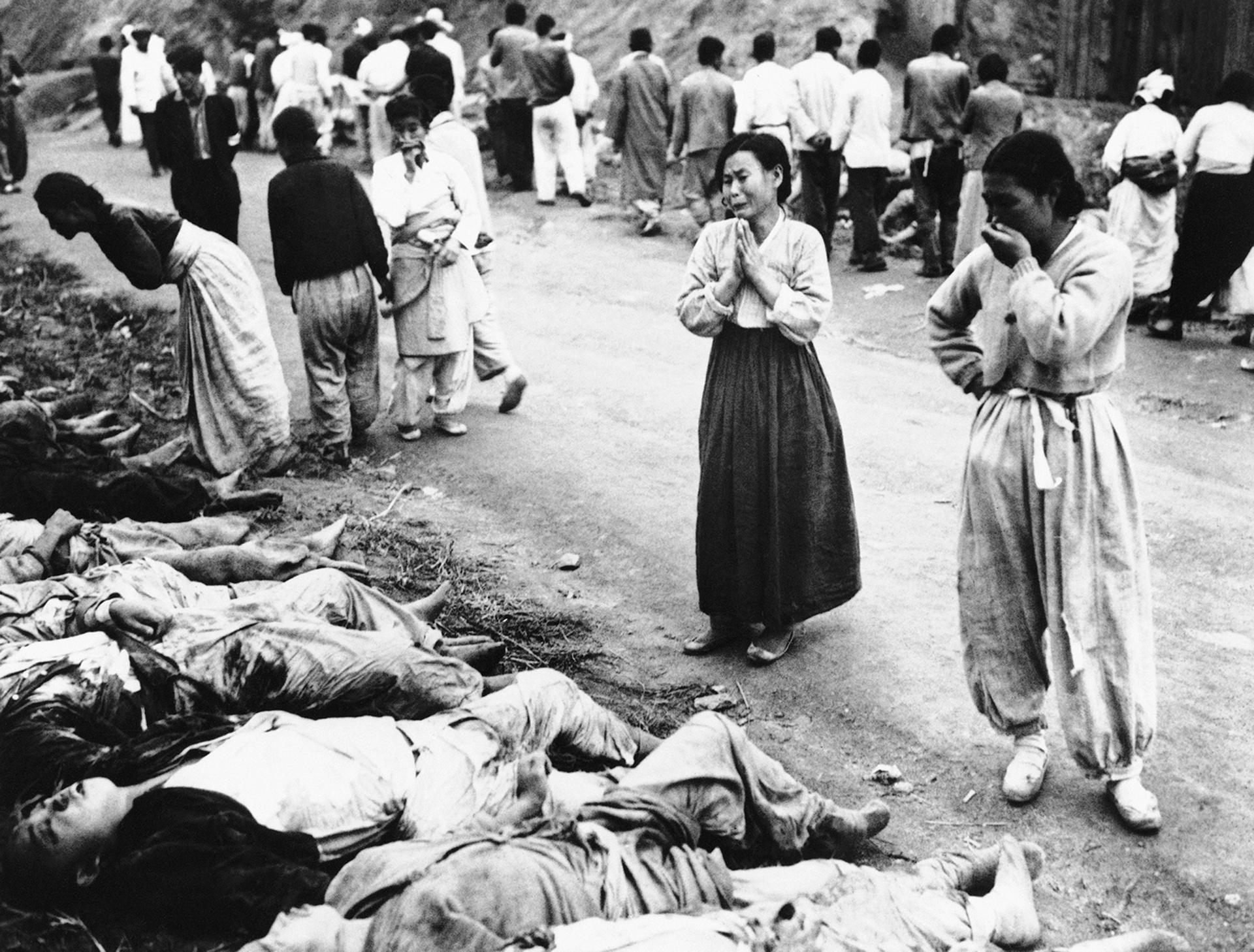 Mujeres coreanas lloran a medida que identifican cuerpos el 28 de octubre de 1953. El ejército dijo que las víctimas estaban entre los prisioneros políticos asesinados por asfixia por los comunistas fuera Hambung, Corea. El Ejército dijo que las víctimas eran forzadas a meterse dentro cuevas que luego eran selladas (AP)