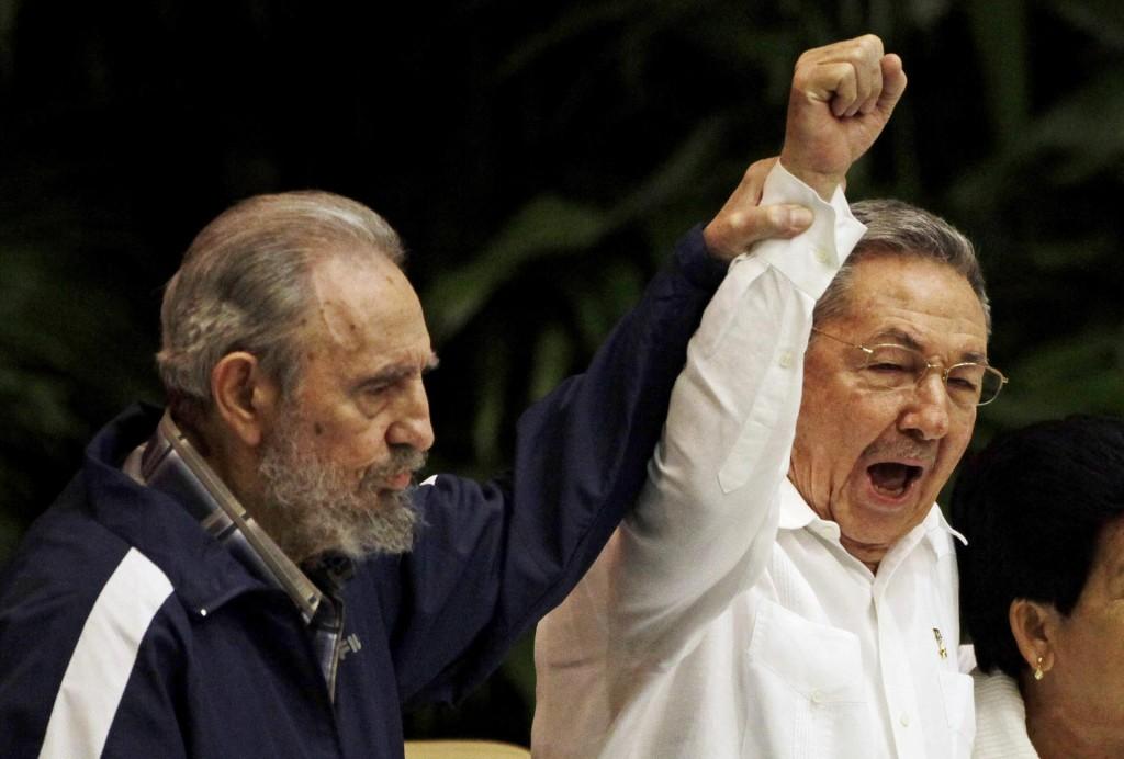 Fidel Castro levanta la mano de su hermano Raúl Castro y cantan el himno internacional del socialismo durante el sexto Congreso del Partido Comunista en La Habana. 19 de abril de 2011 (AP)