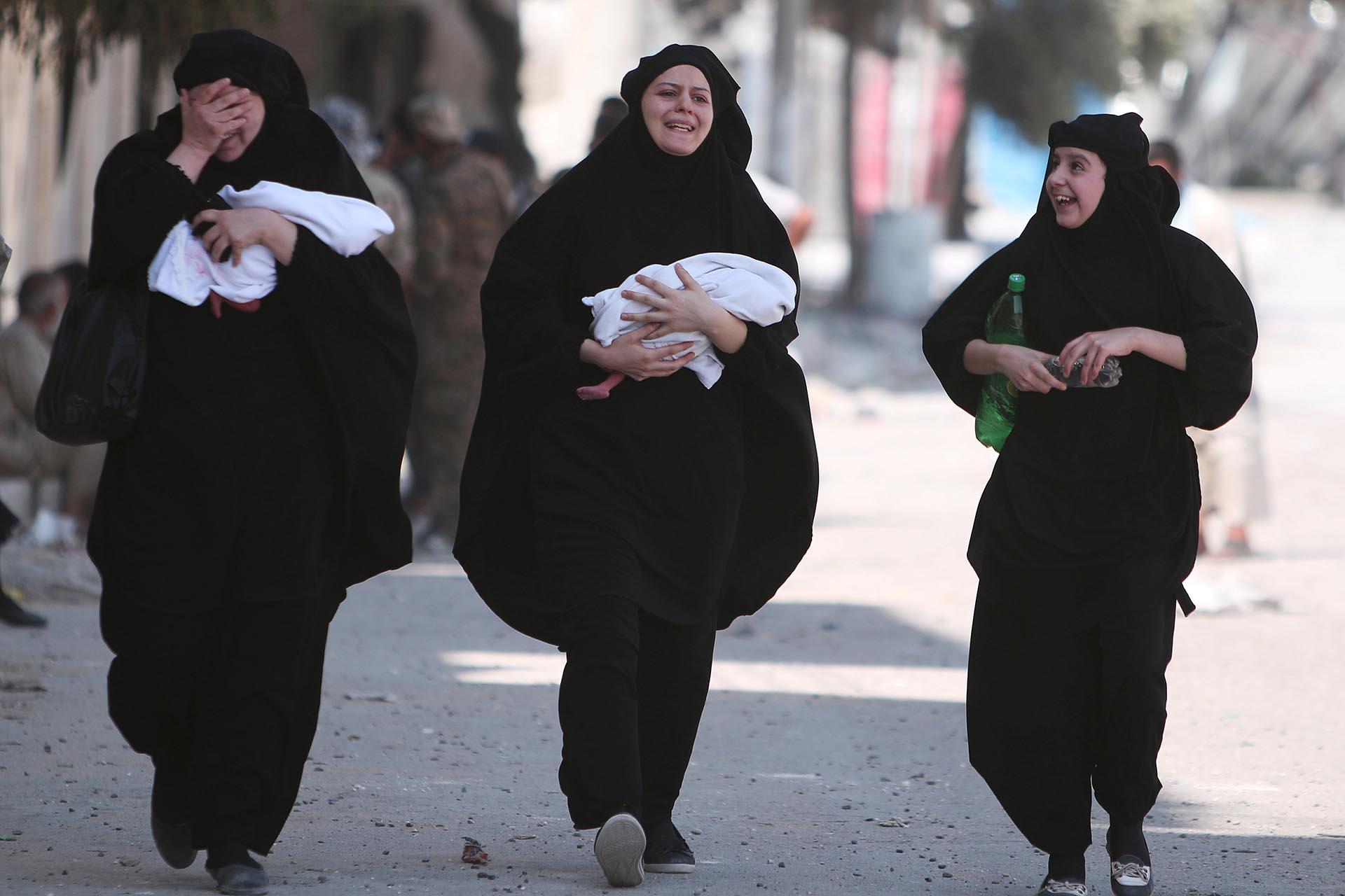 Mujeres lloran de la emoción y llevan a sus bebés recién nacidos en brazos, luego de saber que el Estado Islámico ya no controla su ciudad (Reuters)