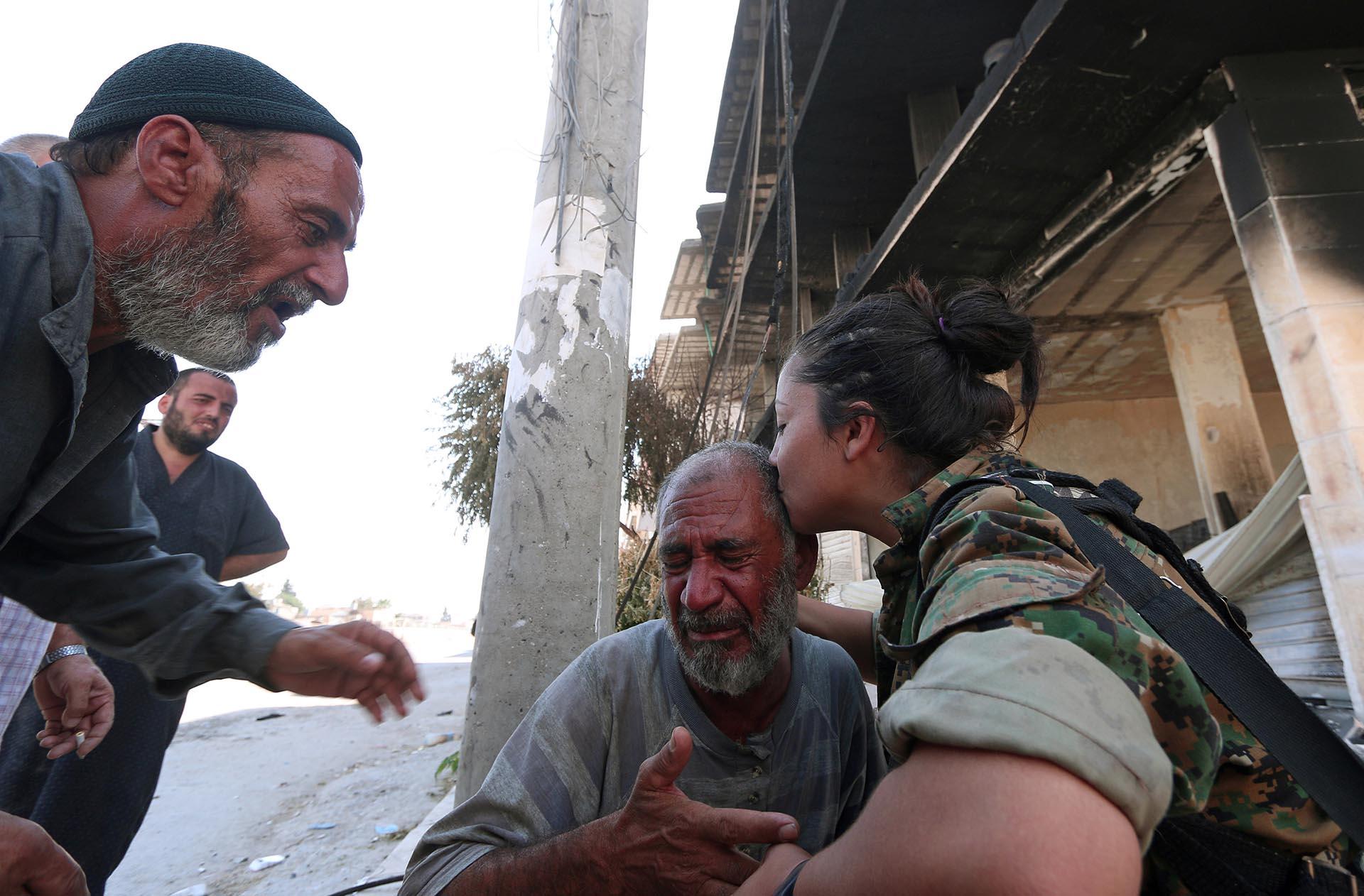 Una combatiente del SDF consuela a un hombre que comprueba que ISIS no está más en en hogar (Reuters)