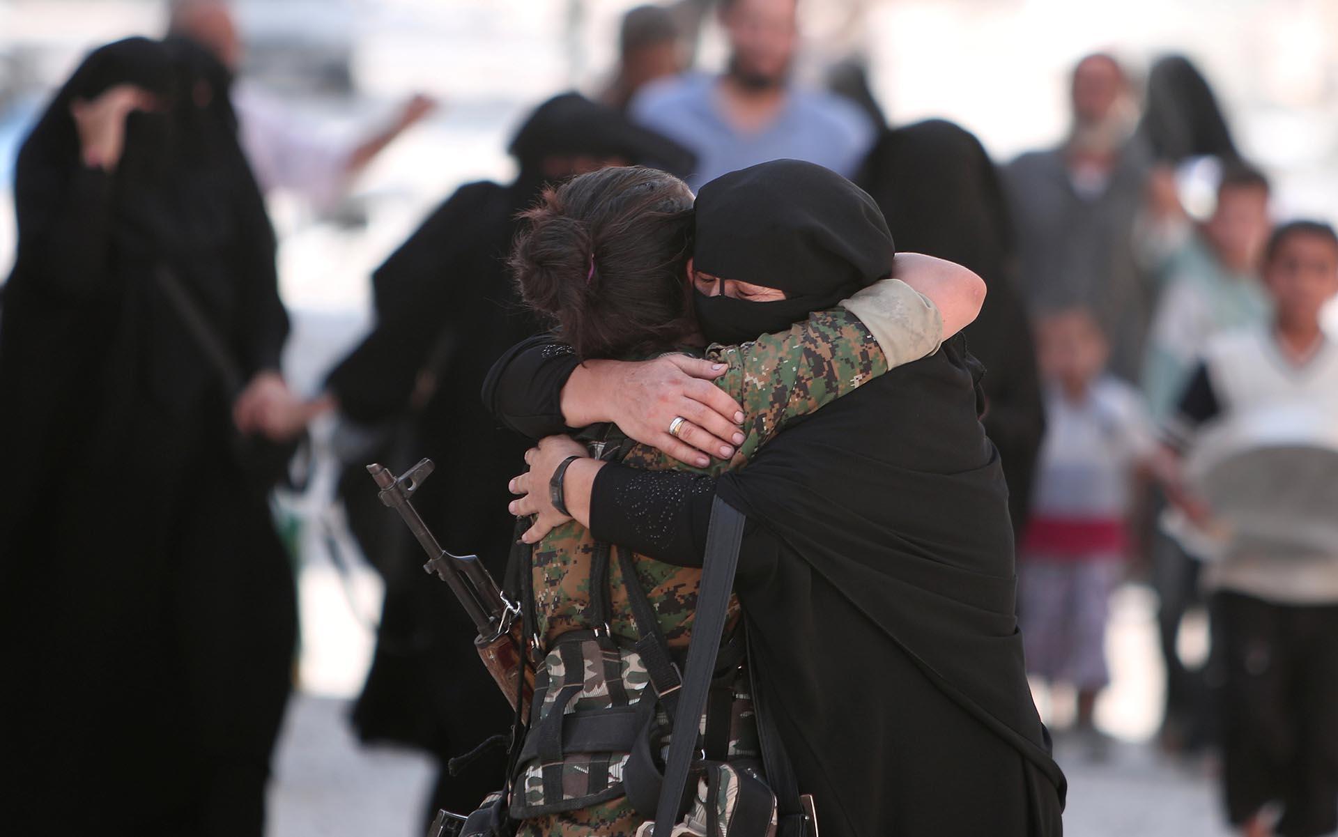 Una mujer abraza a una soldado de las Fuerzas Democráticas de Siria (SDF) luego de ser evacuada de la ciudad de Manbij tras dos años y medio de sufrir el terror de ISIS