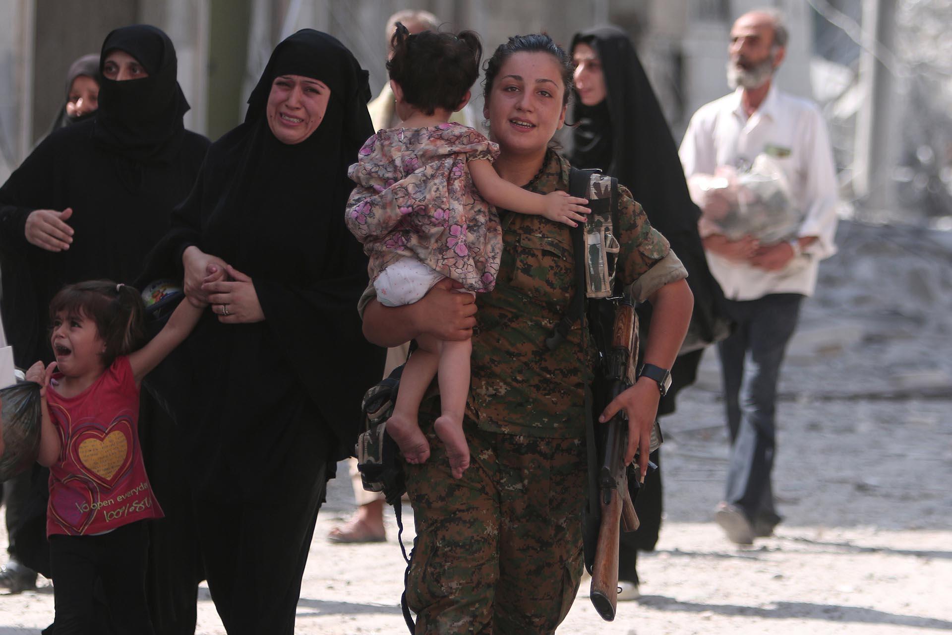 Una combatiente del SDF lleva a una niña, mientras la emoción de las mujeres es evidente al conocer que el Estado Islámico había sido expulsado de Manbij, en Alepo (Reuters)
