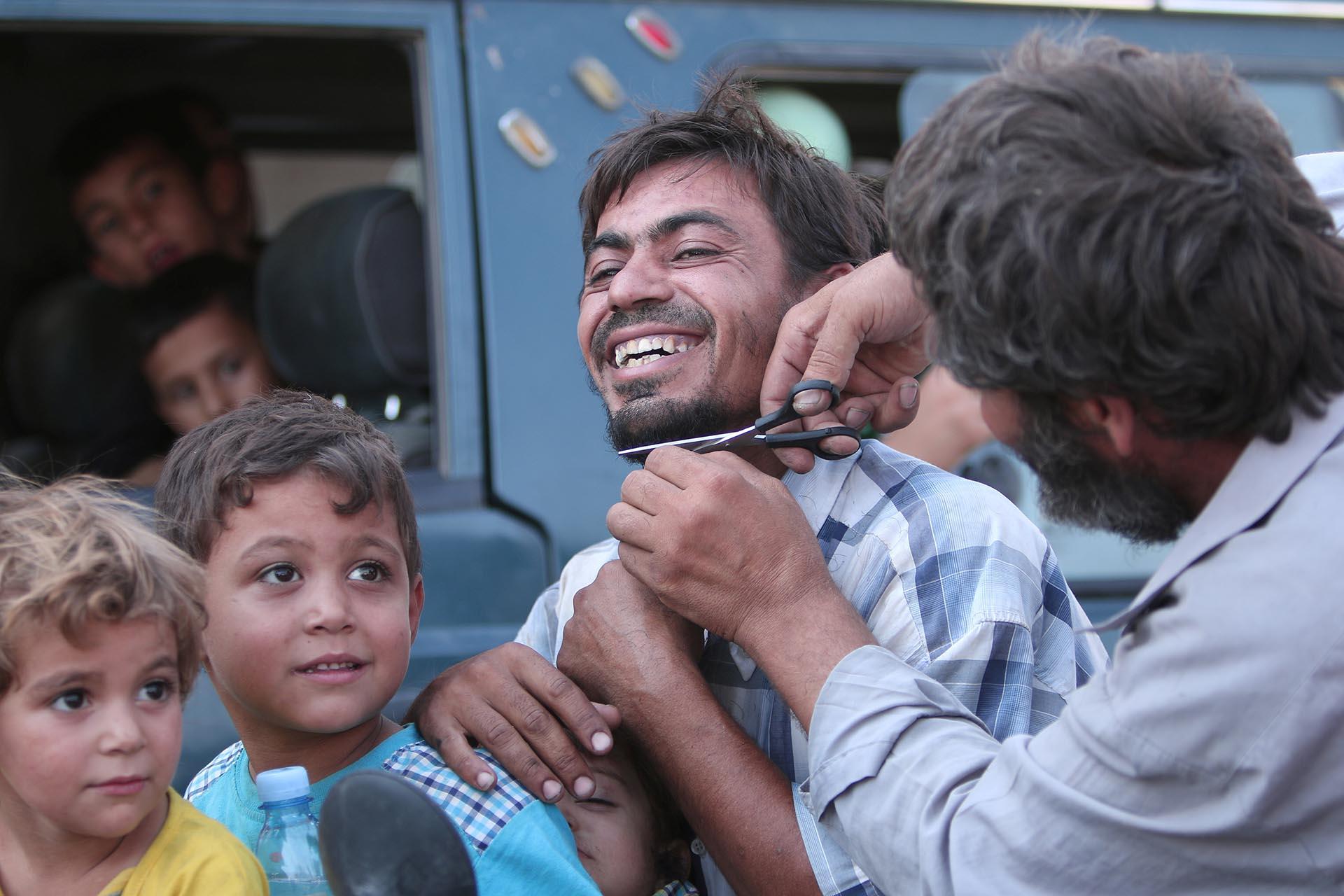 Un hombre corta su barba en público con una sonrisa única. ISIS obligaba a los habitantes de Manbij a usar una barba tupida, como dicta el islam radical (Reuters)