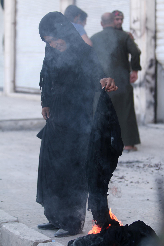 Una mujer quema su niqab luego de saber que el Estado Islámico ya no la obligaría a usarlo. Los terroristas fueron expulsados de la ciudad de Manbij gracias al asedio de una fuerza árabe-kurda con apoyo norteamericano (Reuters)