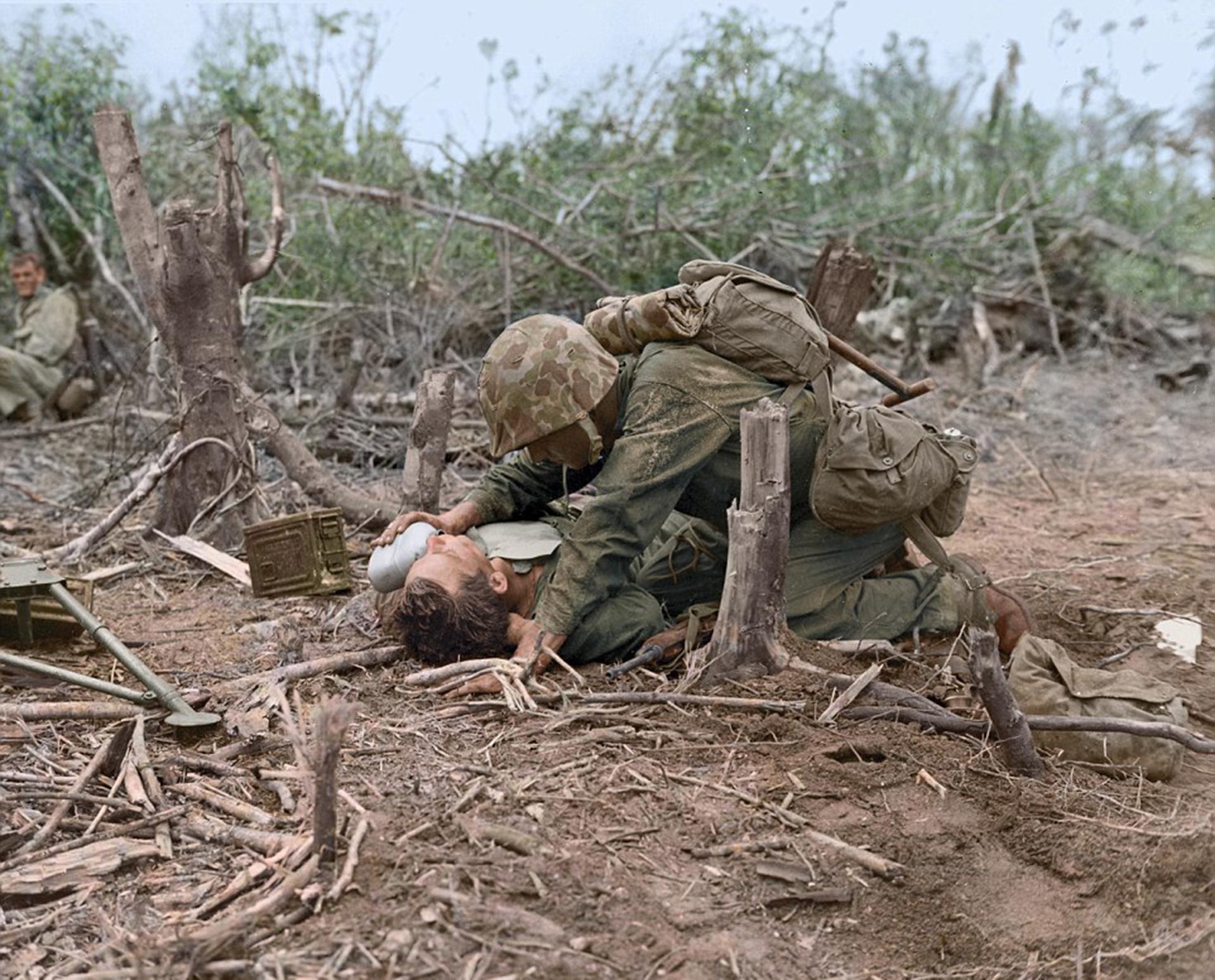 Un marine asiste a un compañero en Iwo Jima, mientras otro, ya sin su casco, observa la dramática imagen
