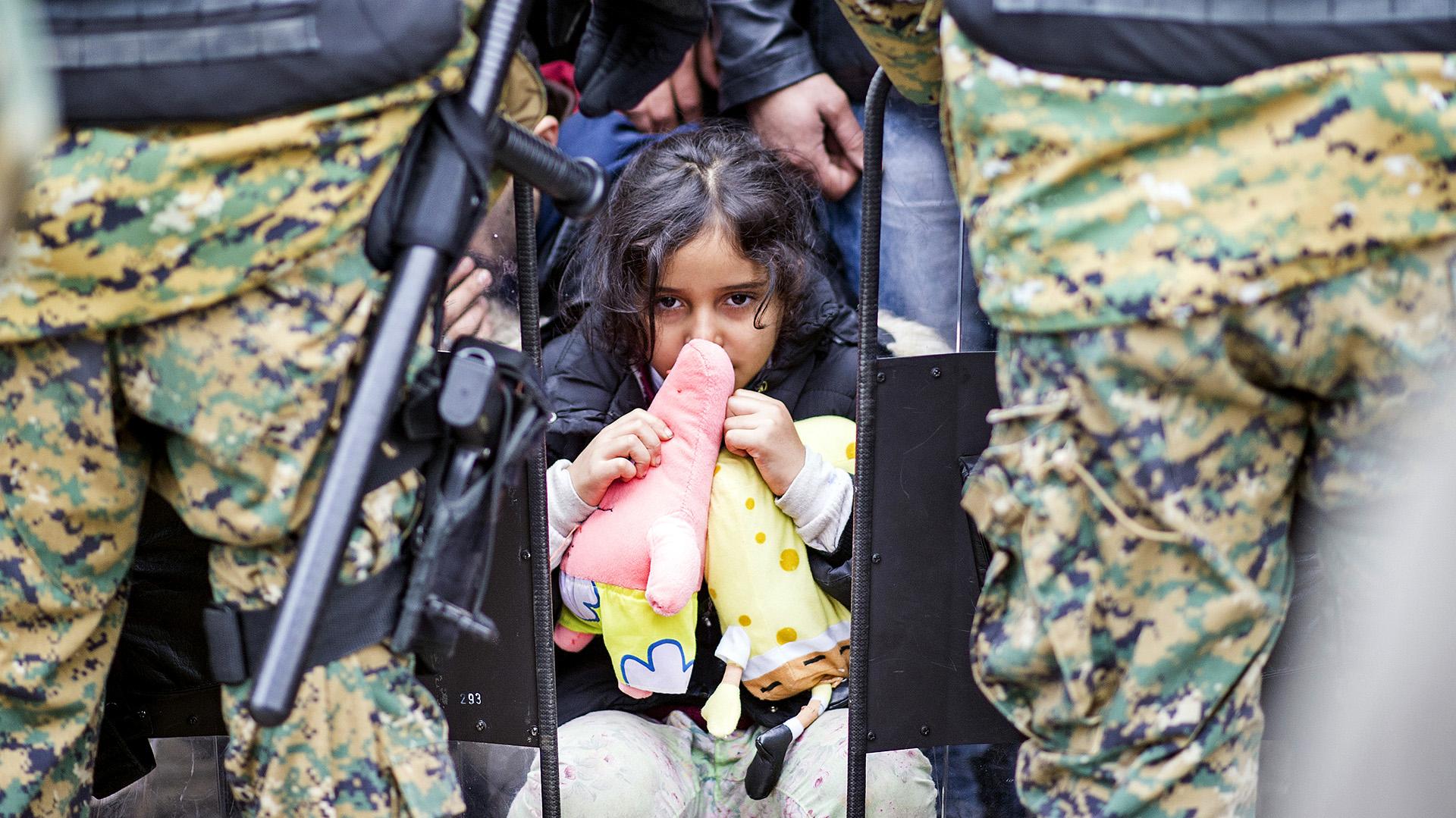 Un niña aguarda entre los oficiales de la policía macedonia para intentar ingresar en Grecia. ROBERT ATANASOVSKI / (AFP)