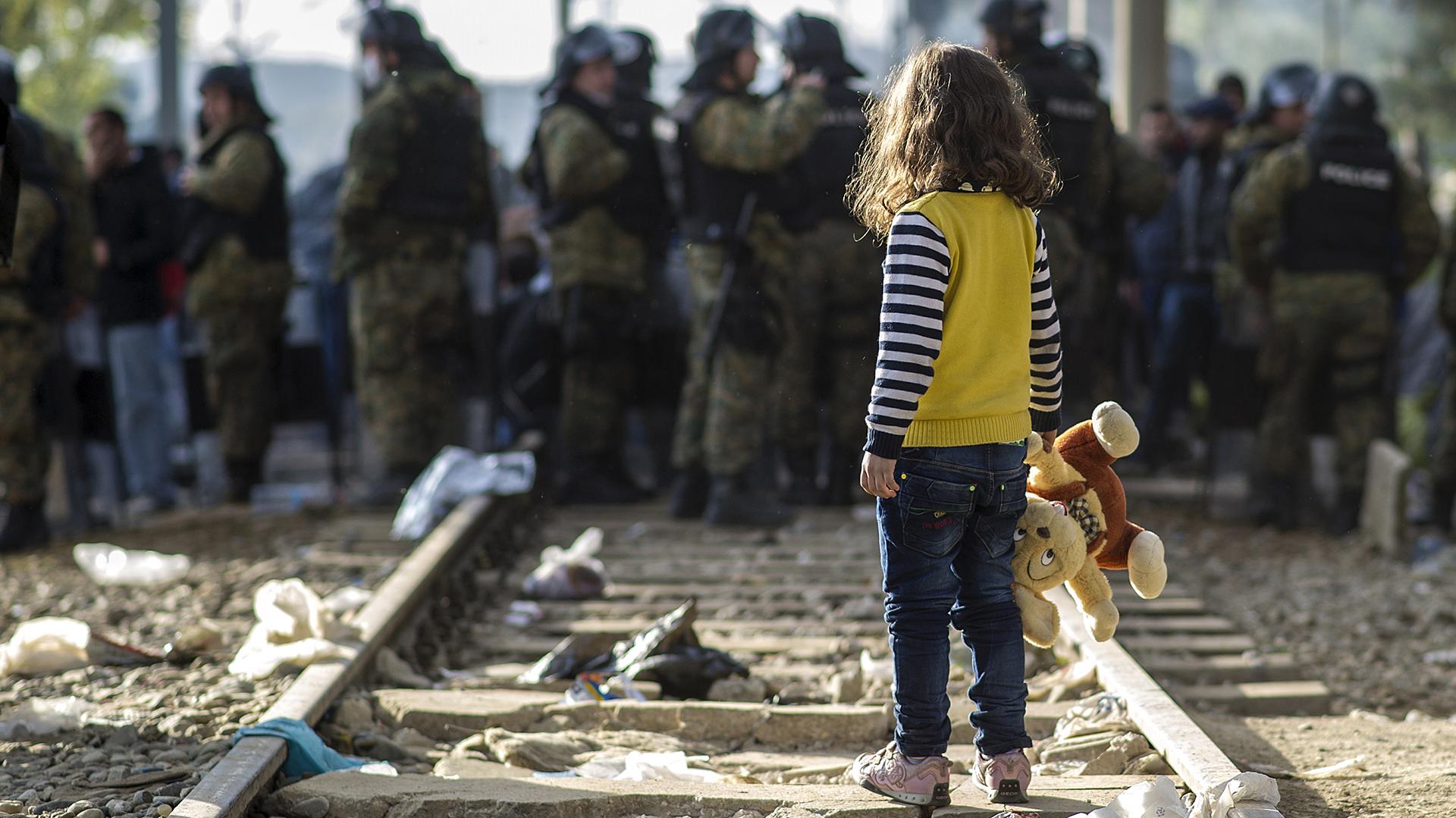 Una niña observa a la policía macedonia mientras impide el paso de inmigrantes hacia Grecia. (AFP)