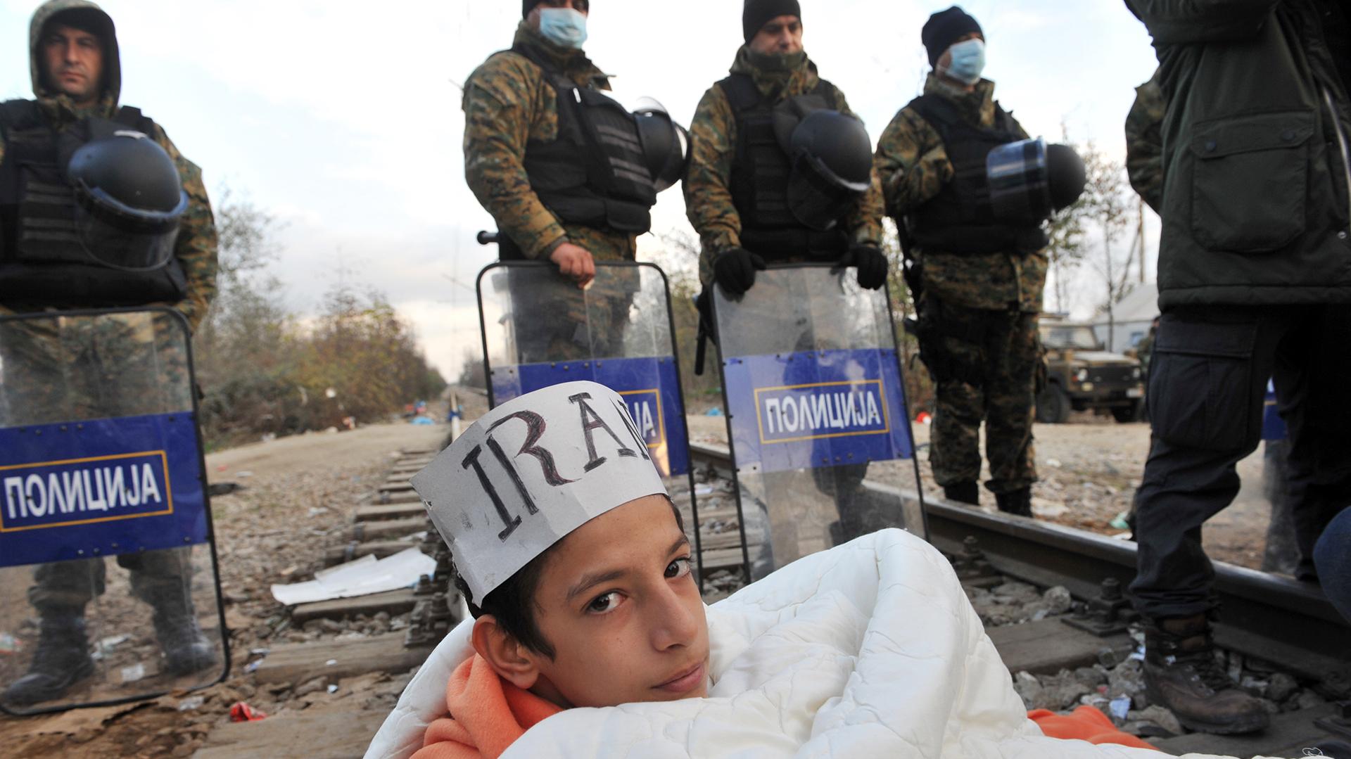 Un refugiado iraní se tiende sobre las vías en la frontera de Macedonia, como protesta para lograr que lo dejen ingresar a Grecia junto asu familia. / AFP / SAKIS MITROLIDIS