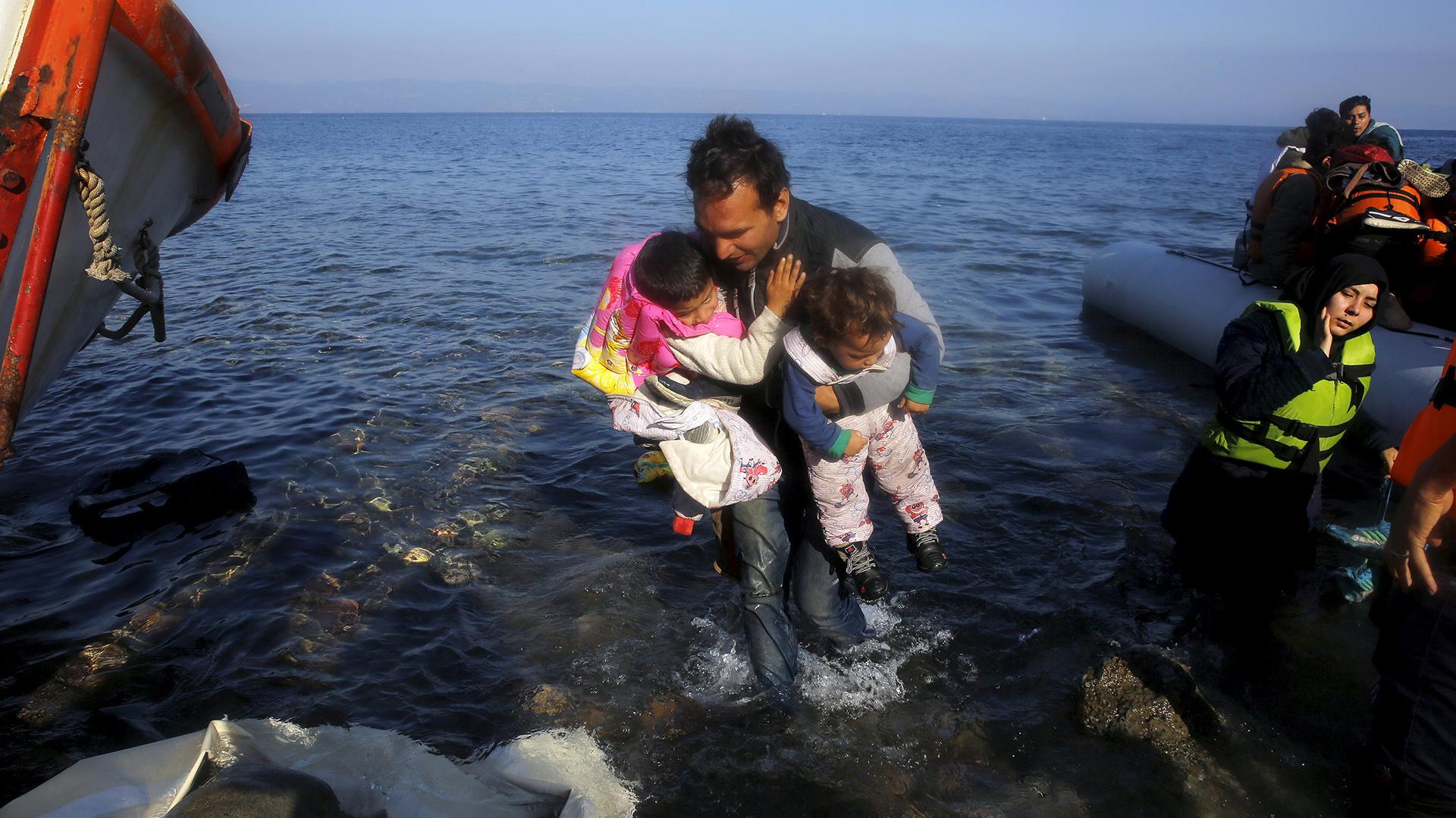 Un inmigrante afgano carga sus hijos luego de arribar en un bote sobrecargado a la isla groga de Lesbos. REUTERS/Yannis Behrakis