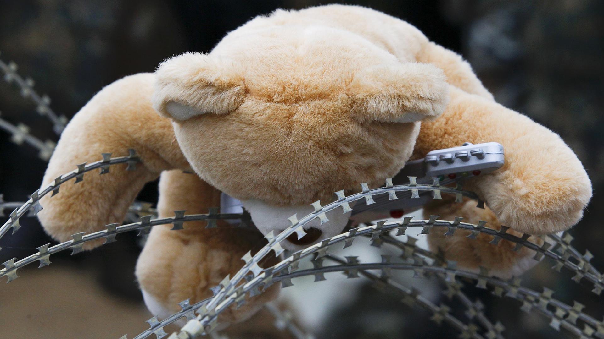 Un oso de peluche olvidado por migrantes en una reja, en la frontera entre Macedonia y Grecia (REUTERS)