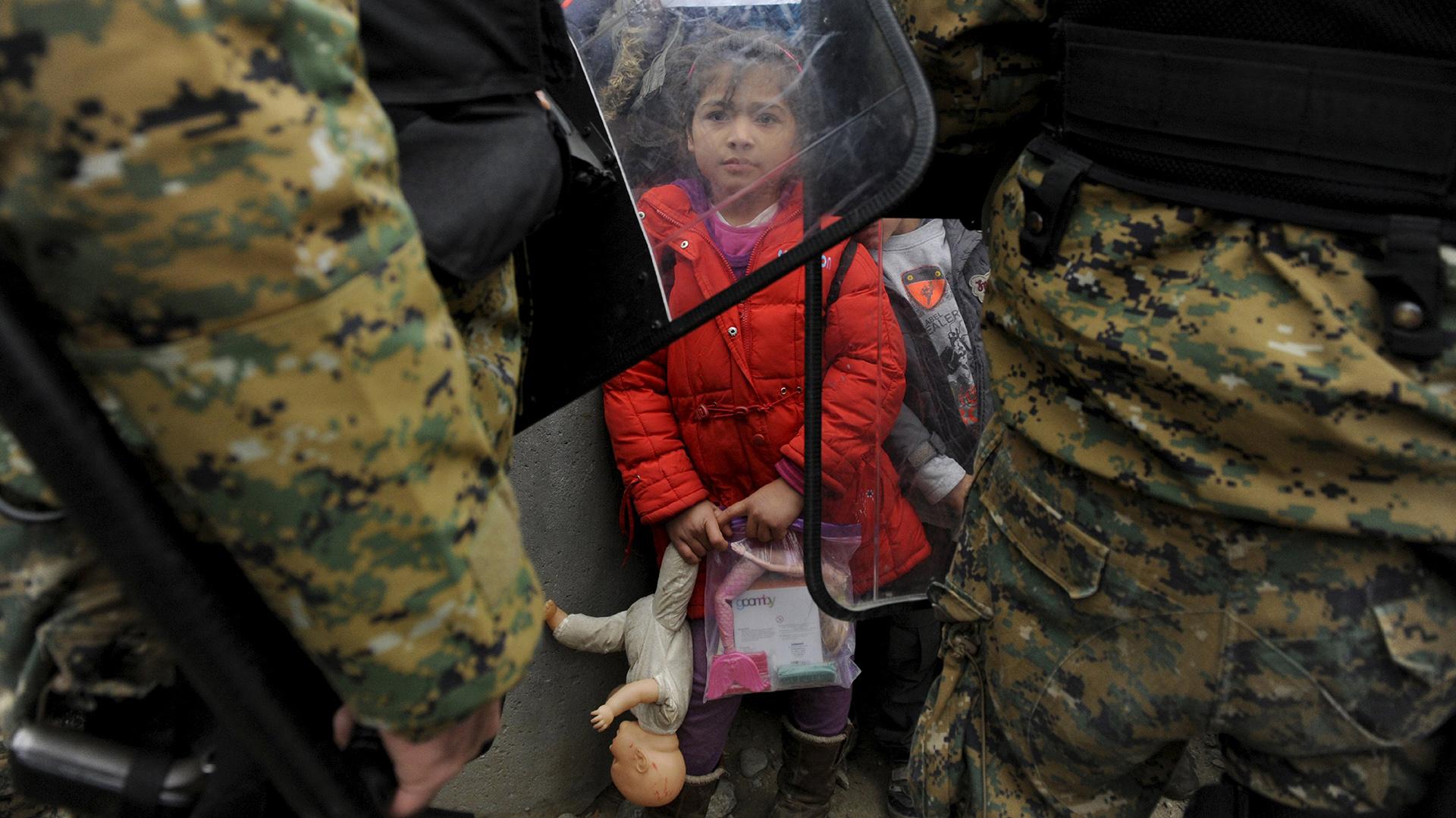 Una niña migrante sostiene sus juguetes mientras la policía Macedonia bloquea el paso en el límite con Grecia. REUTERS/Alexandros Avramidis