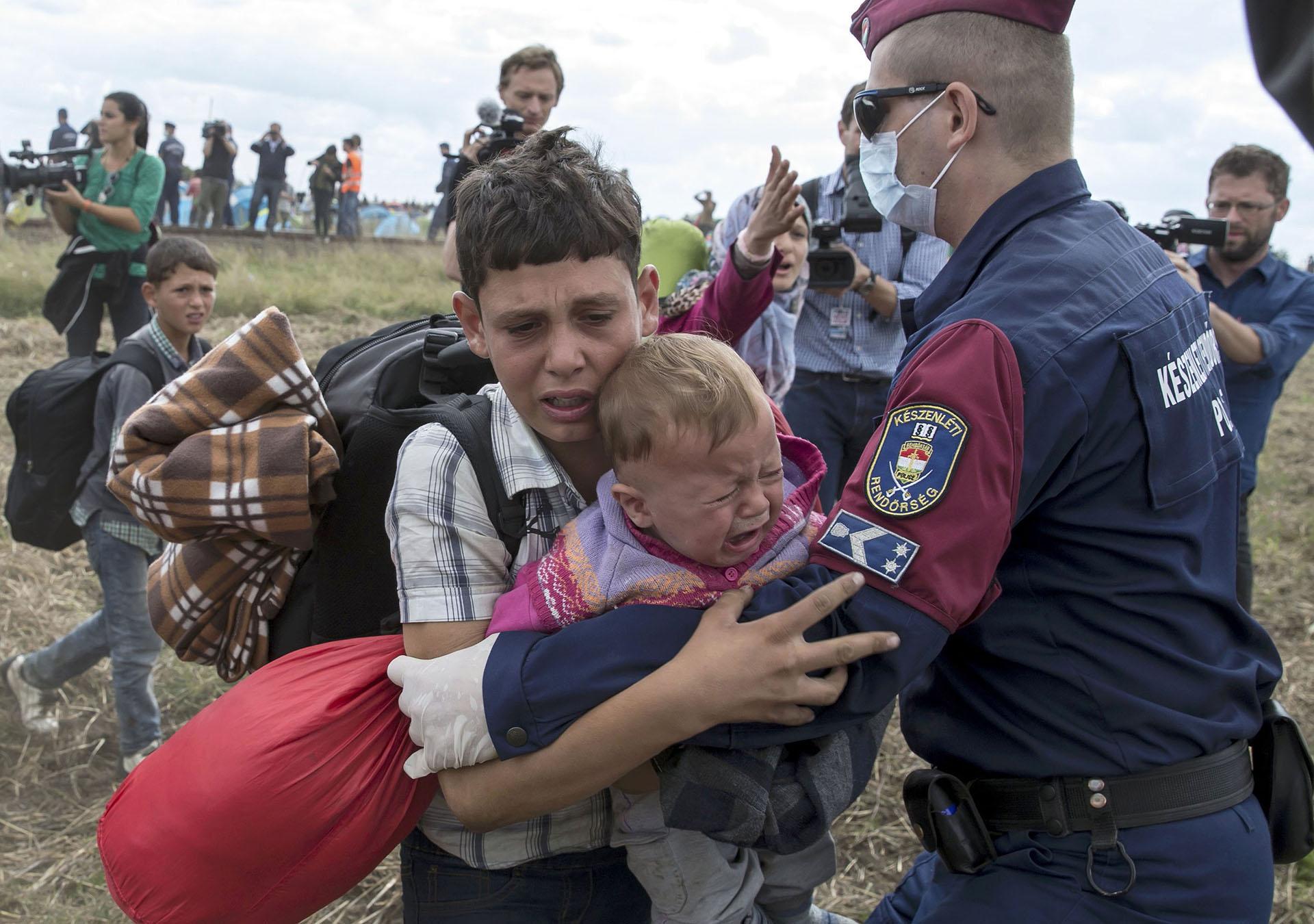 Un policía húngaro trata de detener a un niño migrante que corre cargando un bebé camino a un punto de encuentro. REUTERS/Marko Djurica TPX IMAGES OF THE DAY