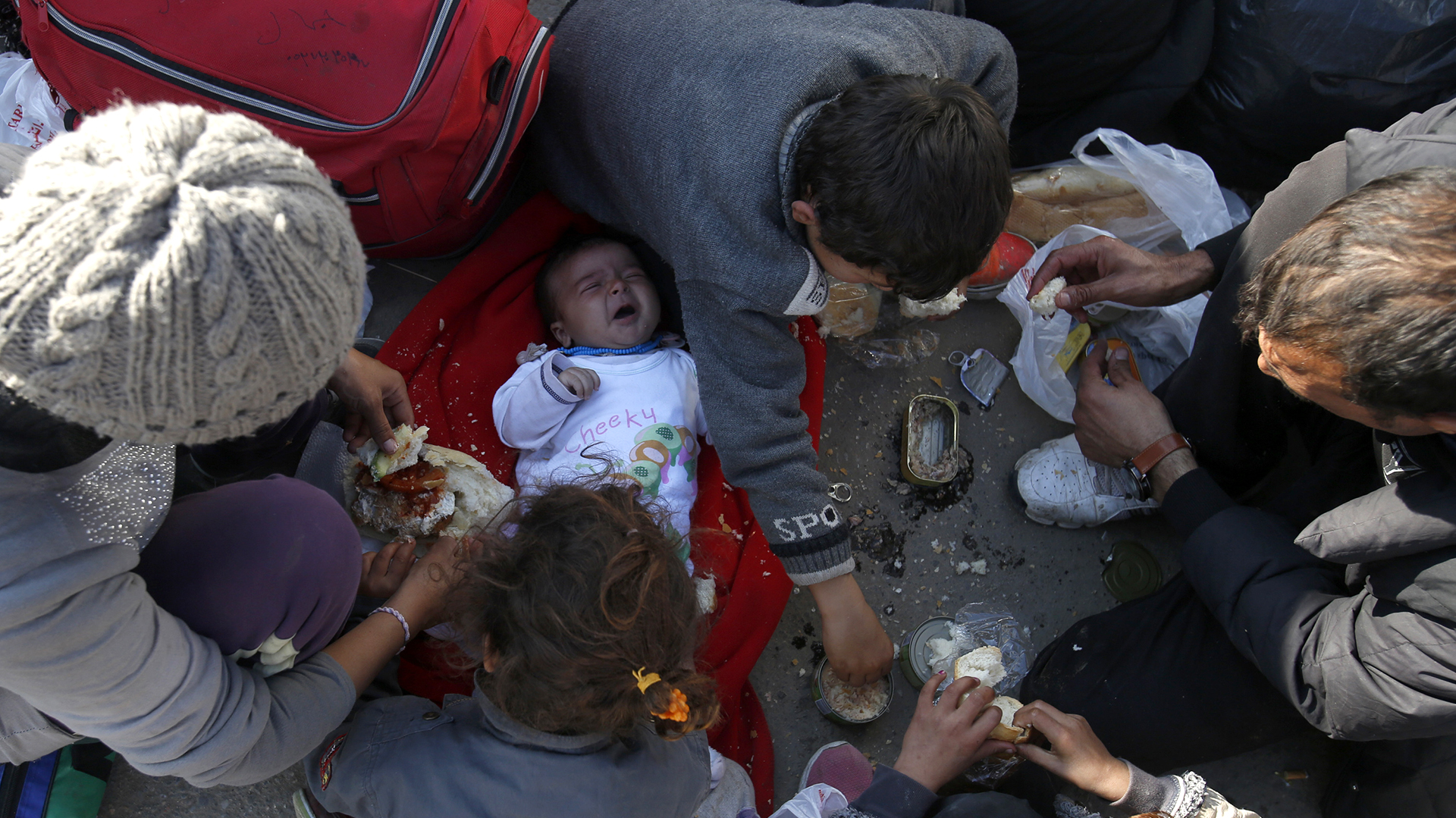 Migrantes comen mientras esperan para registrarse en un centro de refugiados de la ciudad de Presevo, al sur de Serbia. (AP/Darko Vojinovic)