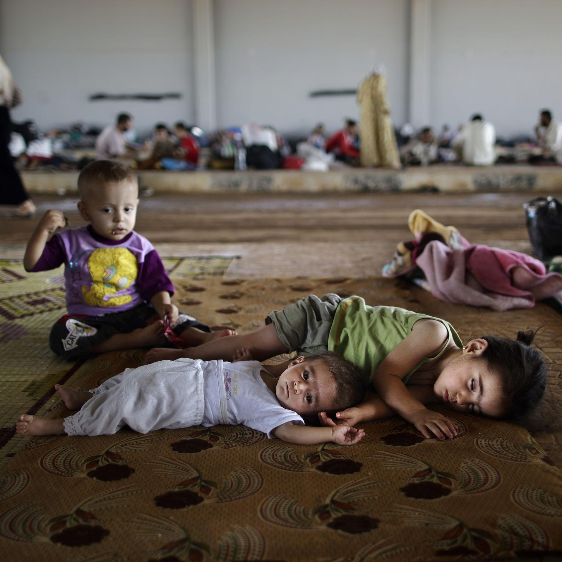 Niños sirios que huyeron de sus ciudades junto a sus familias, aguardan en el puesto aduanero de Bab Al-Salameh para lograr ingresar a un campo de refugiados en Turquía (AFP)