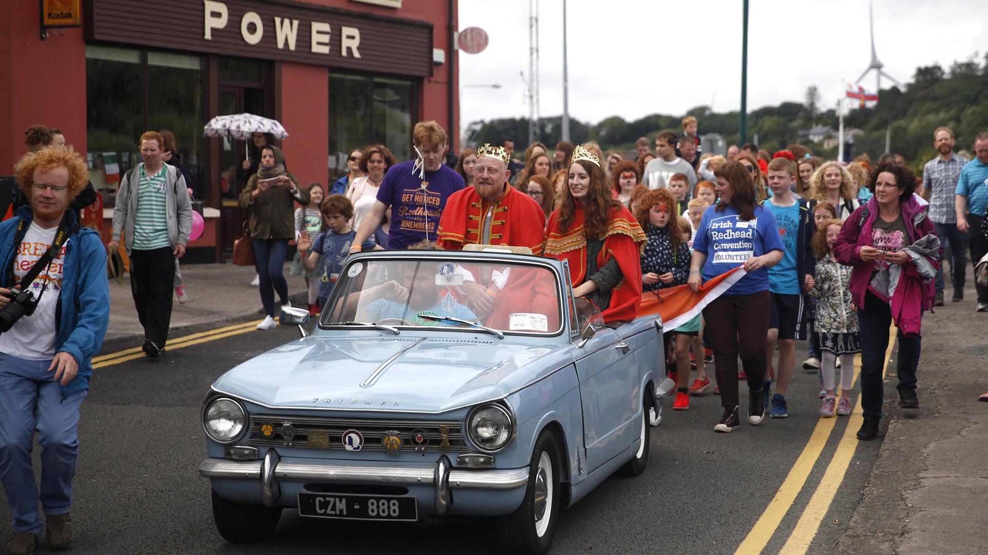 Emma Ni Chearuil and Alan O' Neill, elegidos como los nuevos reyes pelirrojos en la VII Convención Pelirroja Irlandesa, pasean por las calles de Crosshaven, en Irlanda (Peter Morrison/AP)