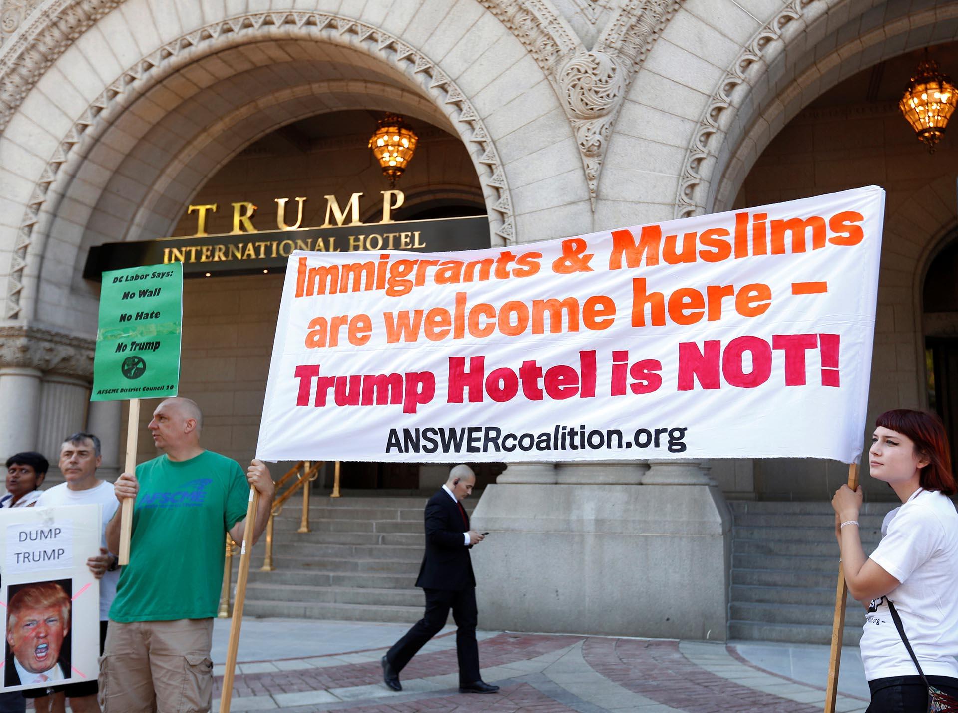 """""""Inmigrantes y musulmanes son bienvenidos aquí. ¡El hotel de Trump, no!"""", una de las consignas de las protestas durante la inauguración del Trump International Hotel en Washington DC (Reuters)"""