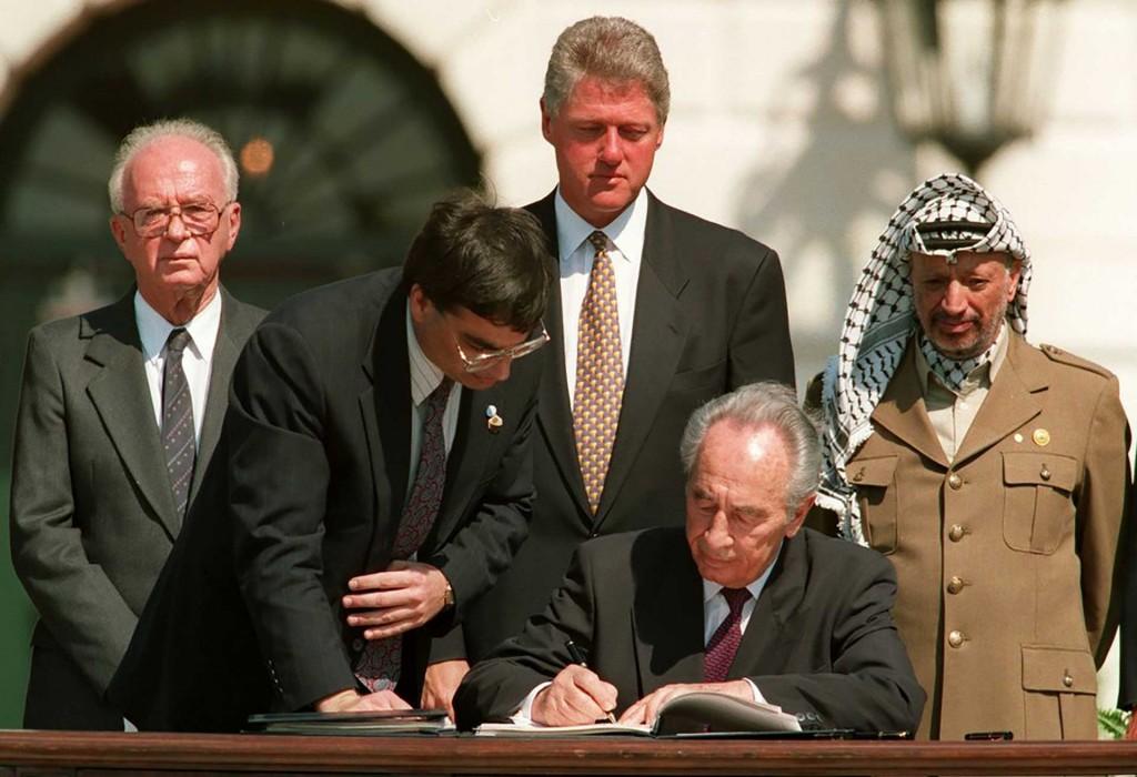 Peres, junto con el líder palestino Yasser Arafat firmando el histórico acuerdo de Oslo en Washington, DC en 1993. Detrás de ellos, oblo observan el entonces Primer Ministro de Israel, Rabin, y el presidente estadounidense, Bill Clinton