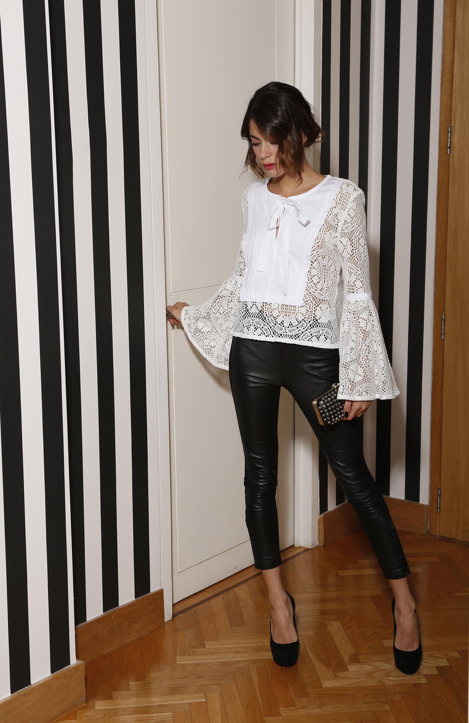 Para la noche: camisola blanca calada estilo boho chic, con leather pants negros, stilettos y clutch con apliques de metal (Santiago Turienzo)