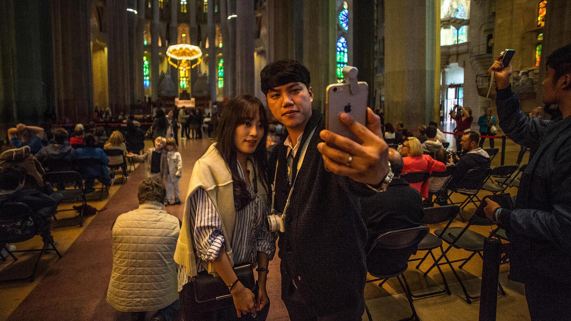 Con el altar mayor como escenario, los visitantes se toman una selfie