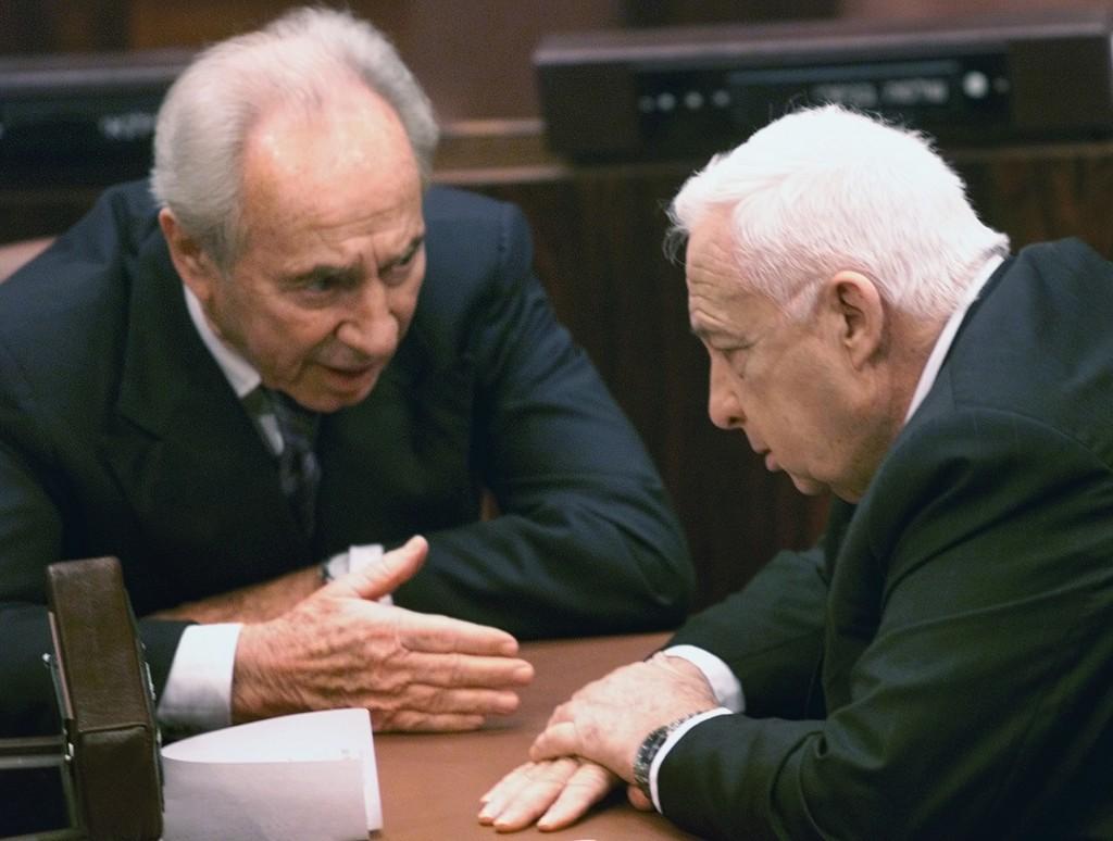 El entonces ministro de Exteriores Shimon Peres en una discusión con el entonces Primer Ministro israelí Ariel Sharon, en la Knesset, el parlamento de Israel, en 2001
