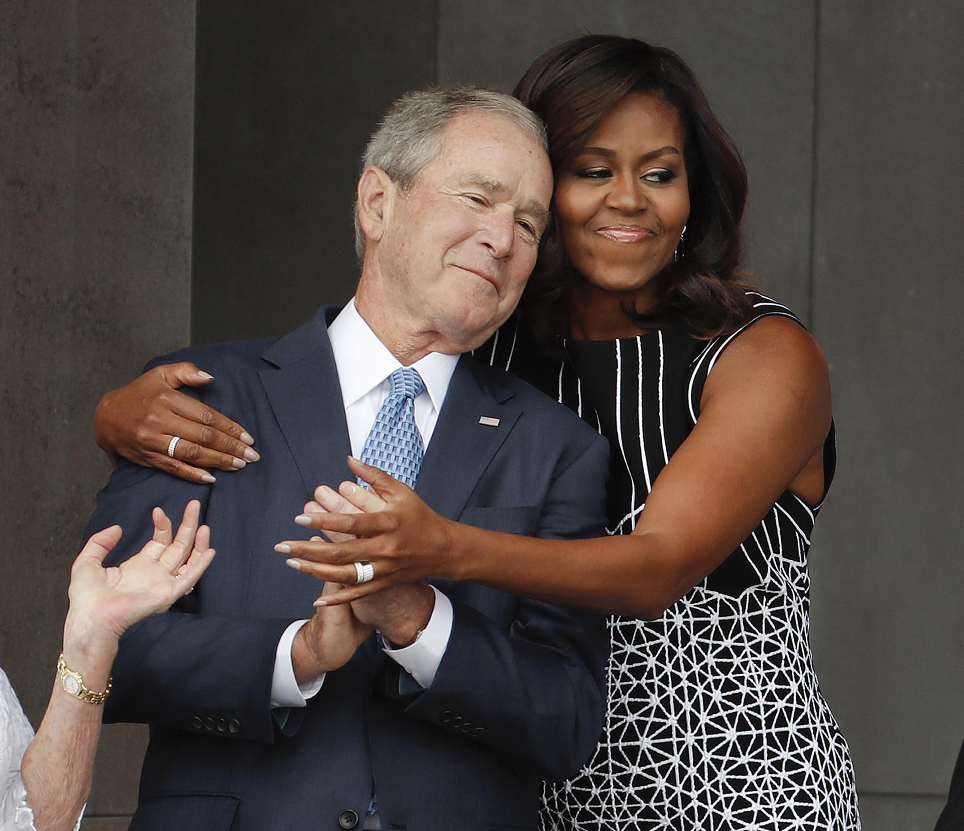 Michelle Obama abraza a George W. Bushen una ceremonia por elSmithsonian Museum of African American History and Culture en Washington el 24 de septiembre de 2016 (AP Photo/Pablo Martinez Monsivais)