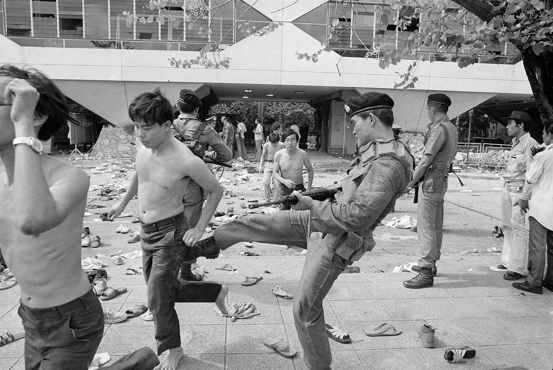 Un soldado da un puntapié a un estudiante luego de la batalla campal en la Universidad de Thammasat (AP)