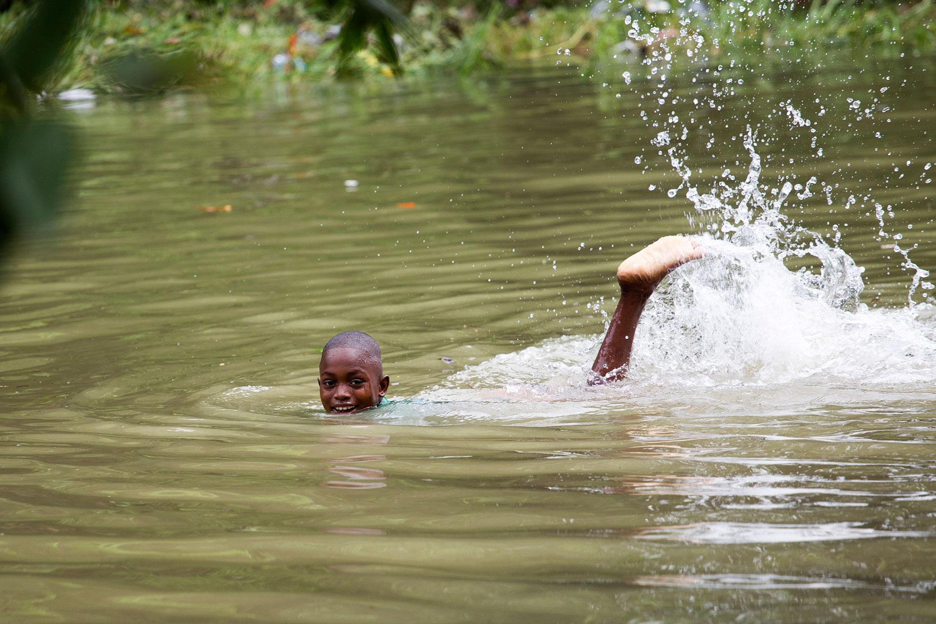 Un nió en Haití sonríe mientras nada en plena inundación (AFP)