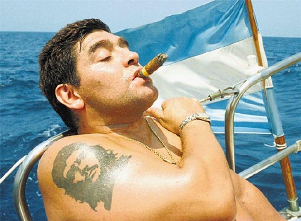Con su tatuaje del Che y una bandera argentina, mientras fuma un habano en un viaje