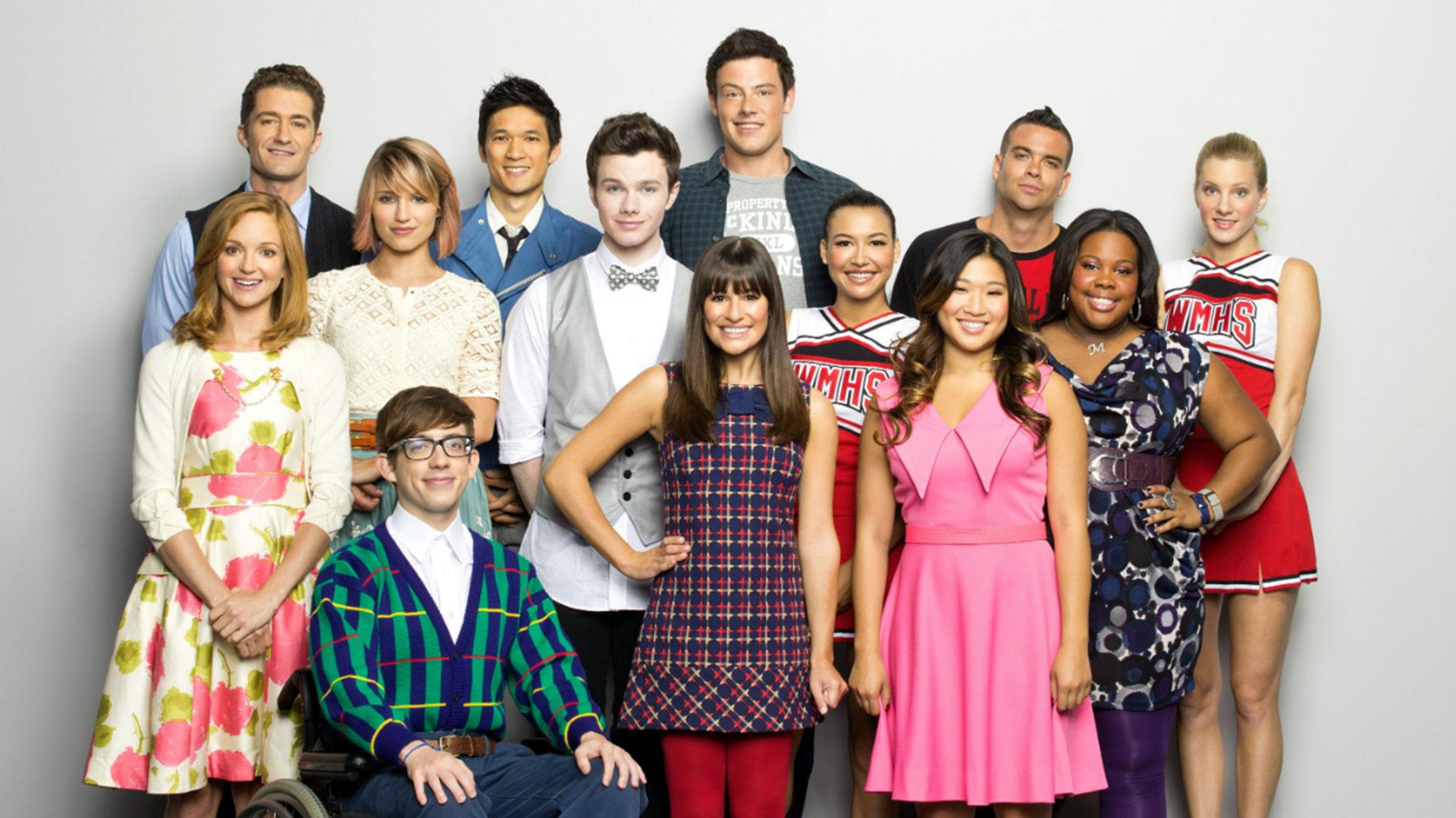 El elenco de Glee, con Corey Monteith en el centro, parado, y Salling a su izquierda, con una remera roja