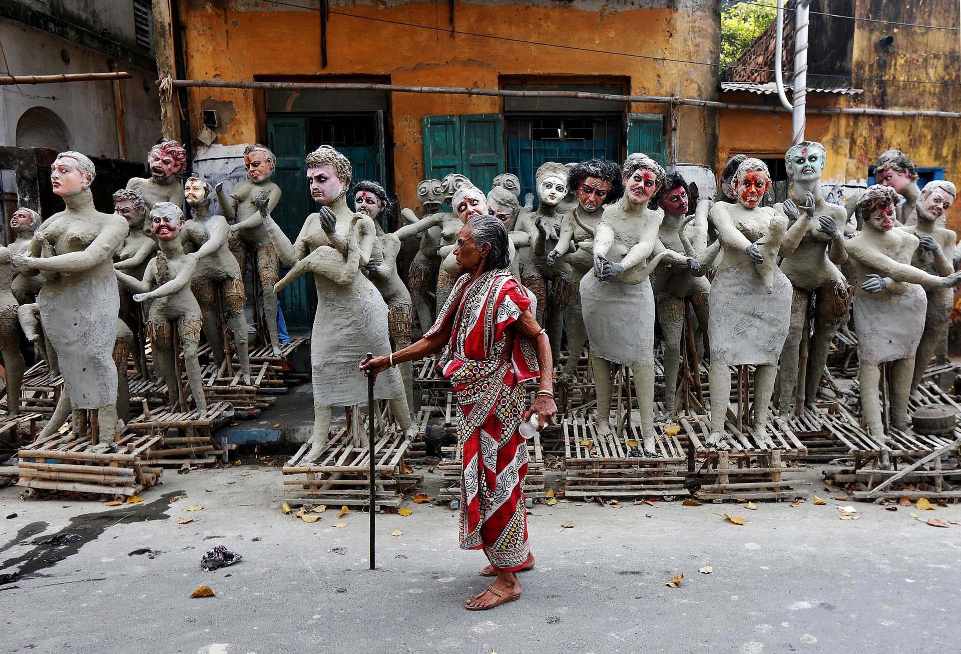 """Una mujer pasa por delante de figuras de arcilla semi-acabados de los personajes mitológicos hindúes """"Dakinis"""" y """"Yoginis"""", que serán adorados junto con la diosa hindú Kali"""