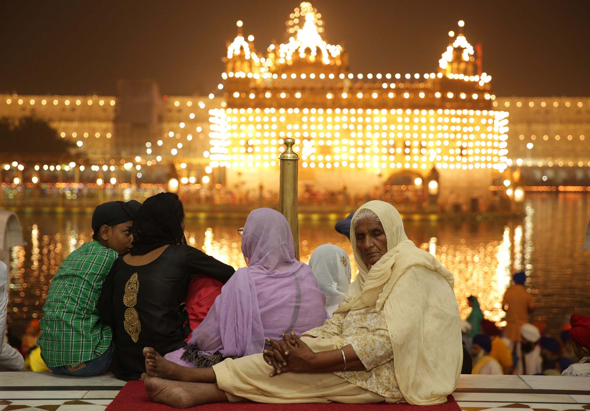 Una anciana escucha himnos religiosos mientras visita el Templo Dorado, el santuario más sagrado de los santuarios Sikh