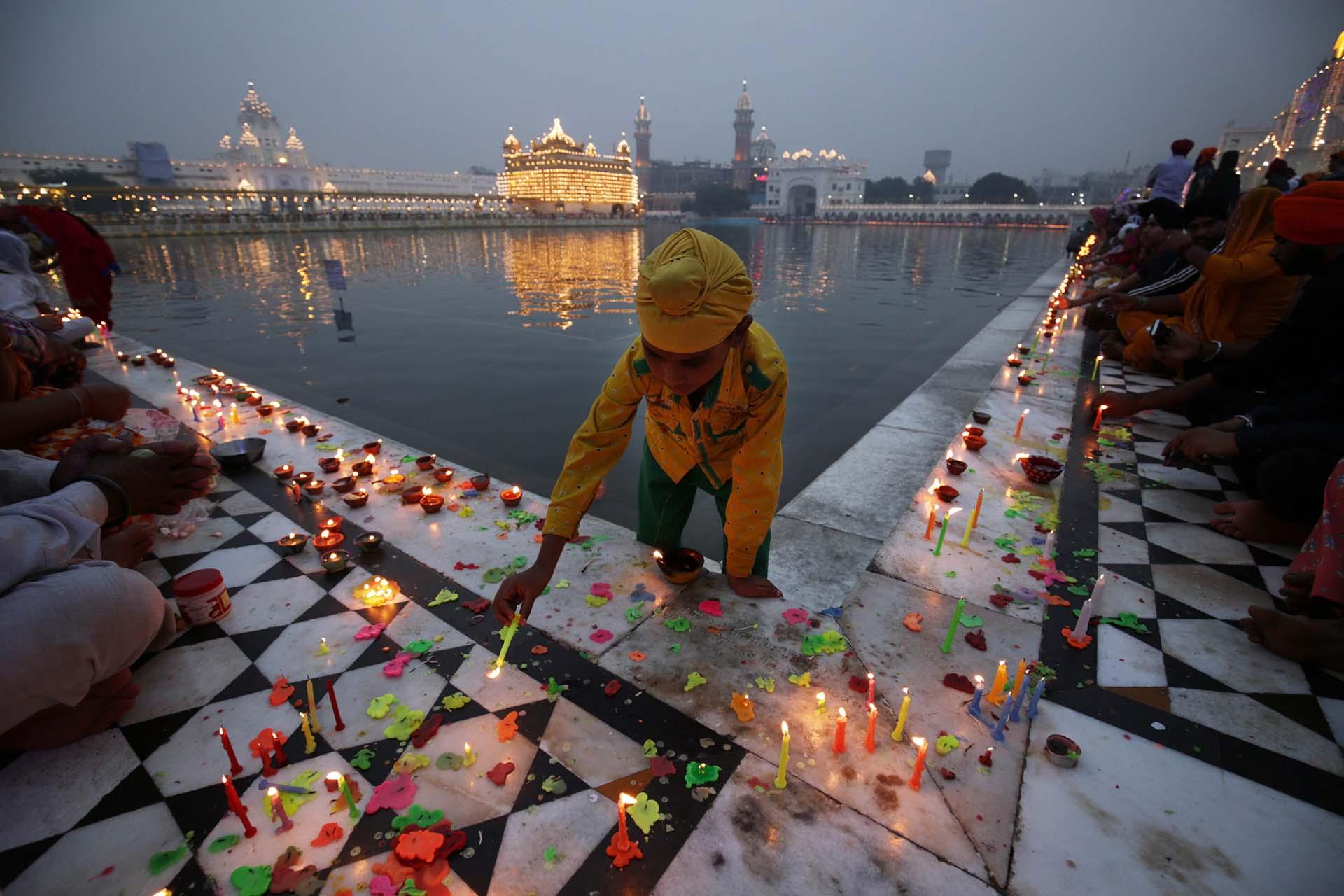 Un niño sikh enciende velas cerca del estanque sagrado en el templo de oro, con motivo del festival de Diwali y de Bandi Chorh Diwas en Amritsar, la India