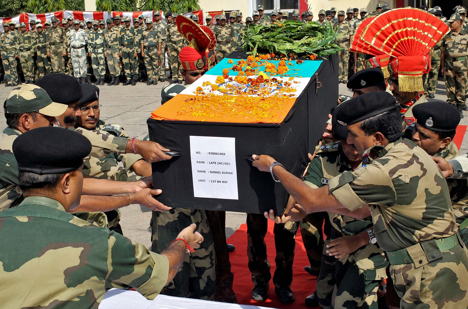 Los oficiales de la Fuerza de Seguridad Fronteriza de India (BSF) colocan el ataúd de su colega caído, que murió después de bombardeos a través de la frontera entre la India y Pakistán