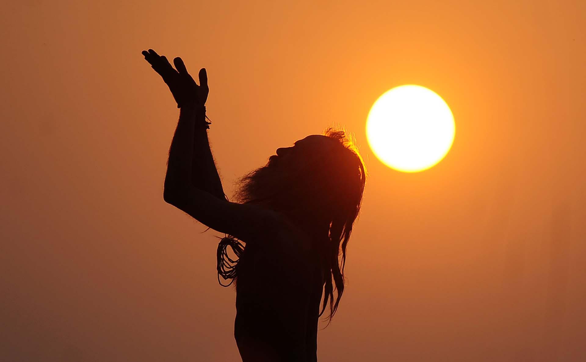 Un sadhu indio – hombre santo – realiza el yoga en la salida del sol, en Dashashwamedh Ghat en Varanasi