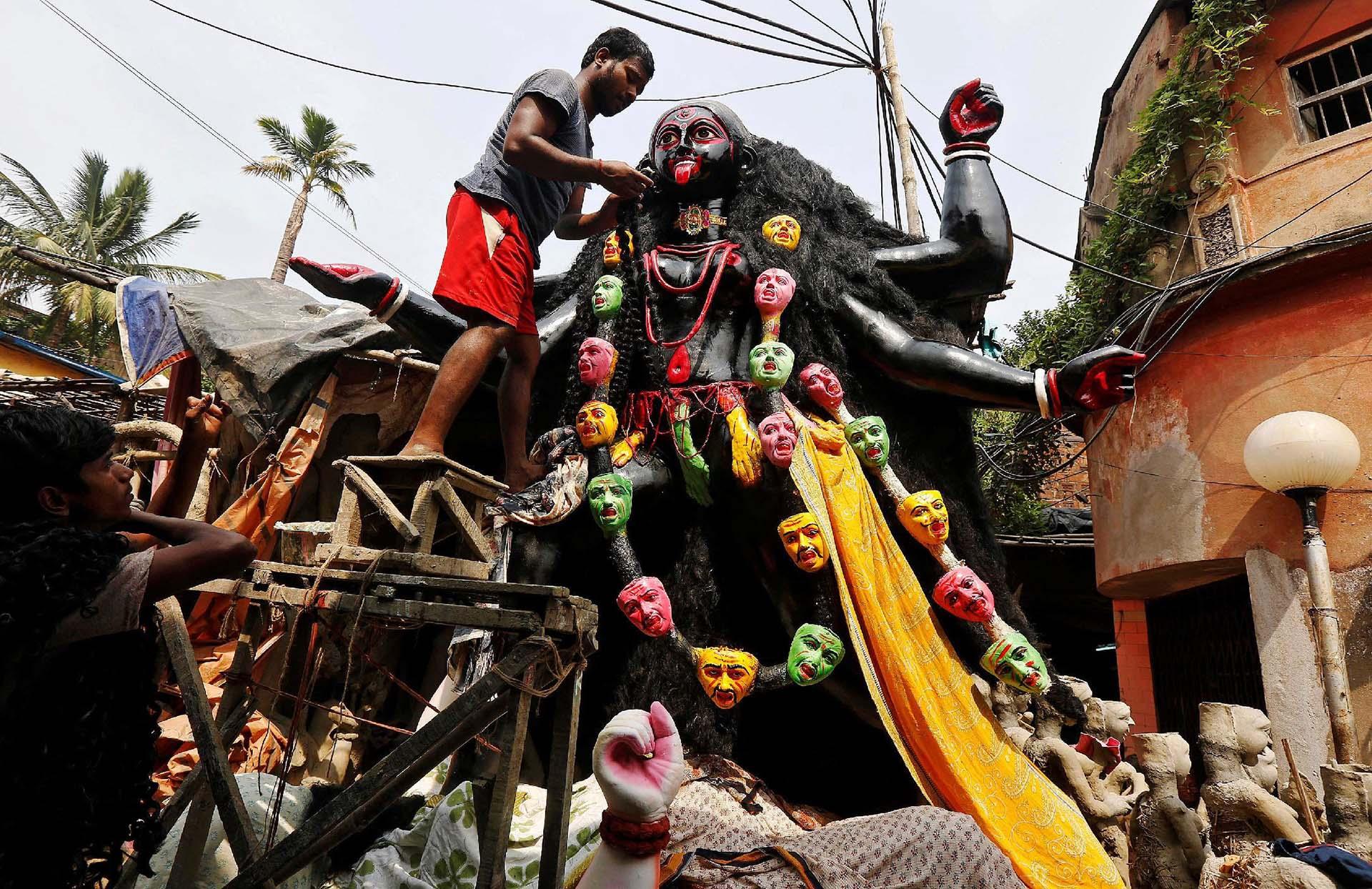 Un artista pone el pelo artificial en una figura de la diosa hindú Kali, antes del festival de Kali Puja en Kolkata