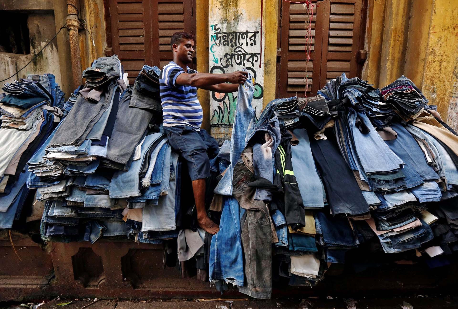 Un vendedor en un mercado de segunda mano de ropa, en Kolkata, India