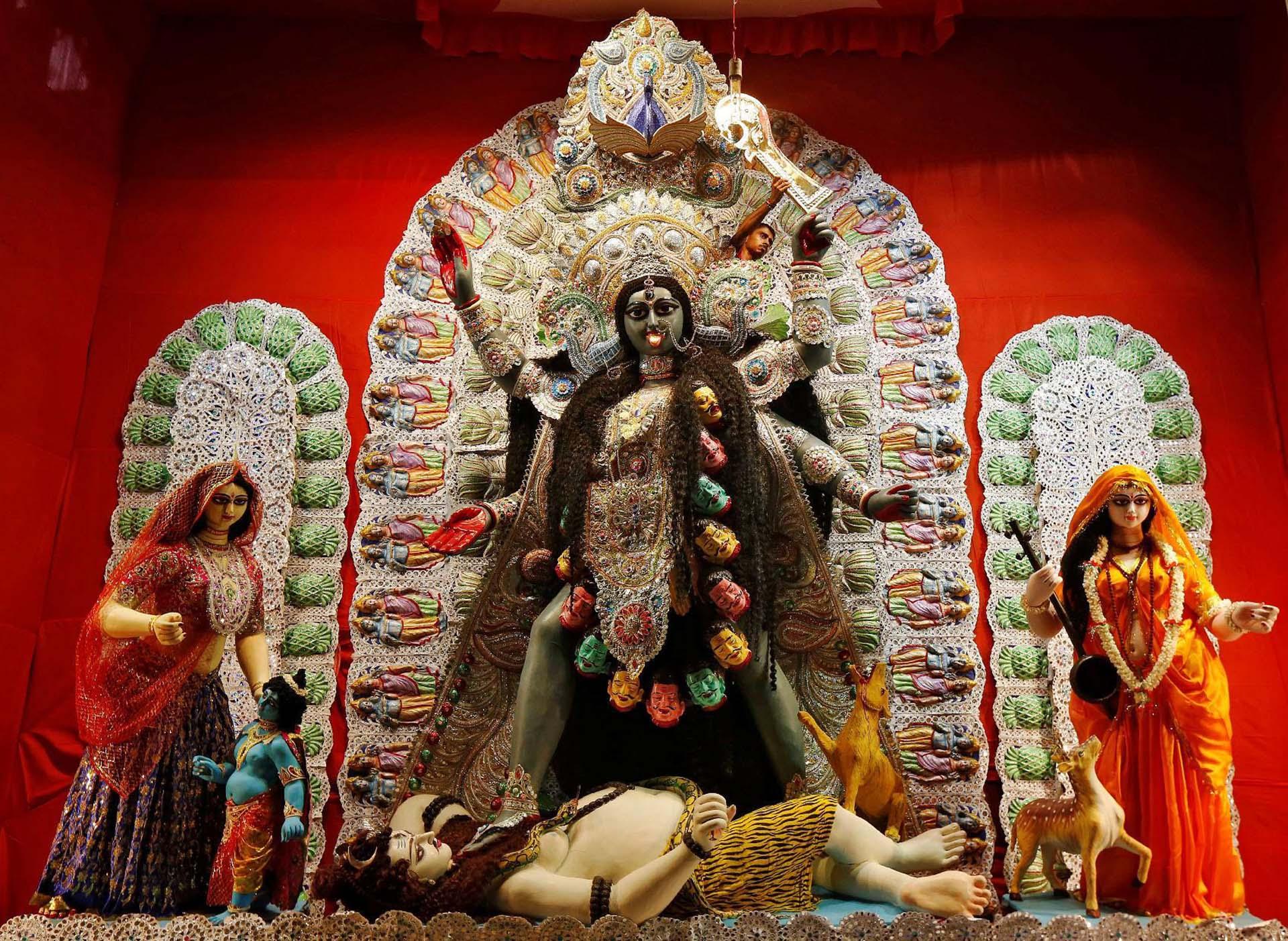 Un artesano finalizando una figura de la diosa hindú Kali dentro de un pandal, una plataforma temporal, en Kolkata, India