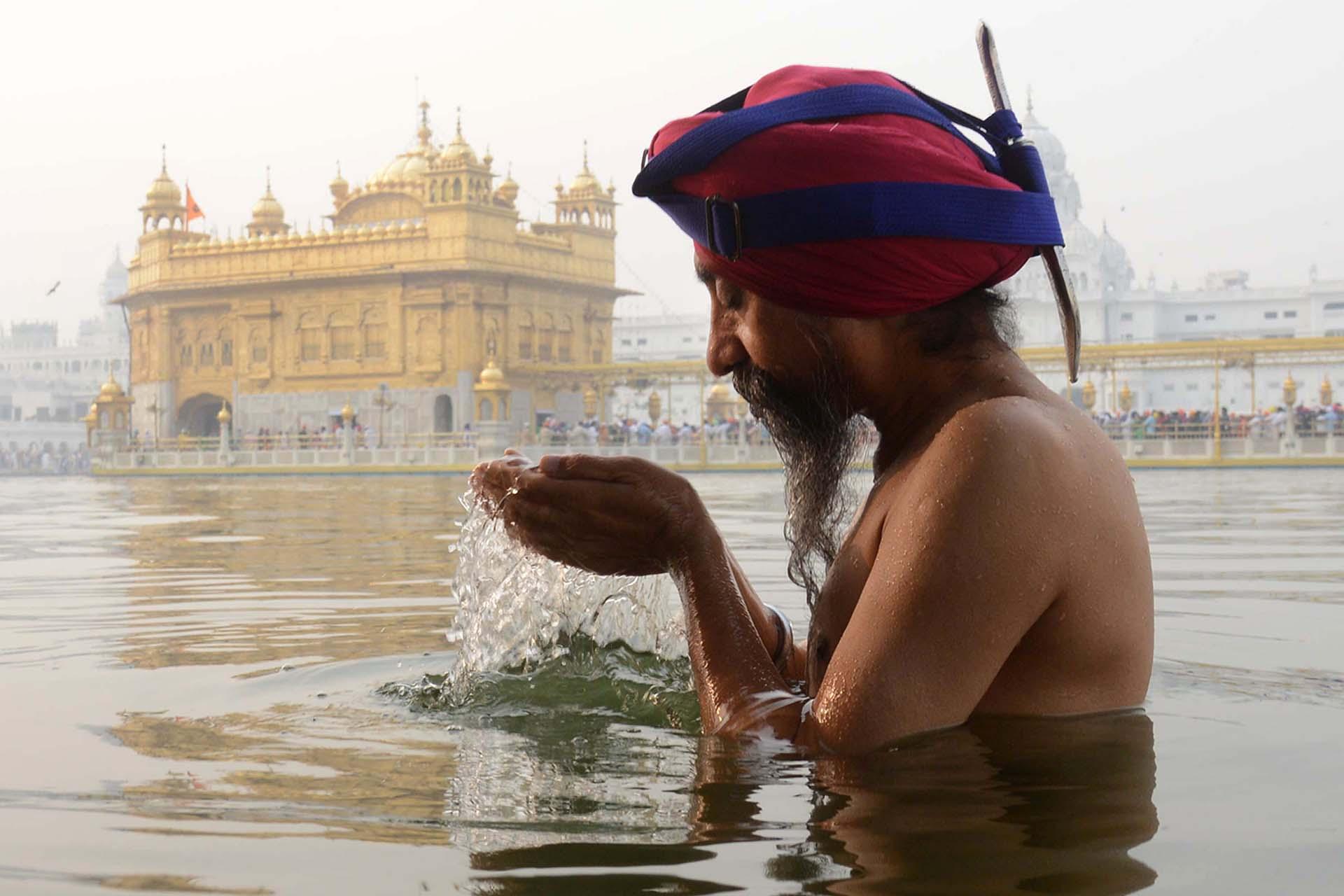 Un devoto sikh se baña en el santo sarovar (tanque de agua) con motivo de Bandi Chhor Divas, o Diwali, en el Templo de Oro en Amritsar