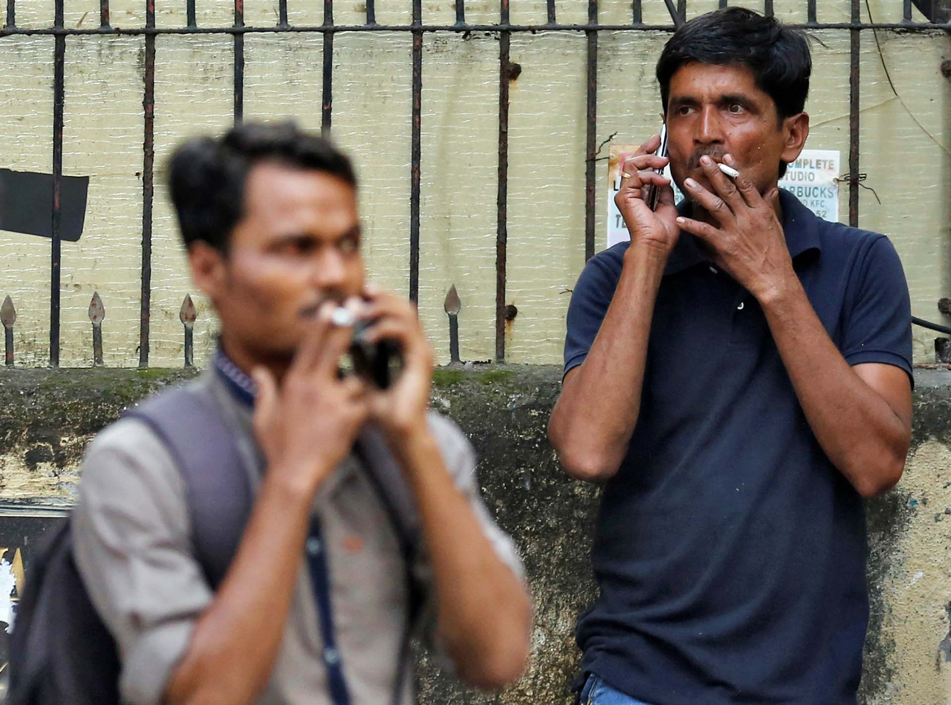Transeuntes fuman en una calle de Mumbai