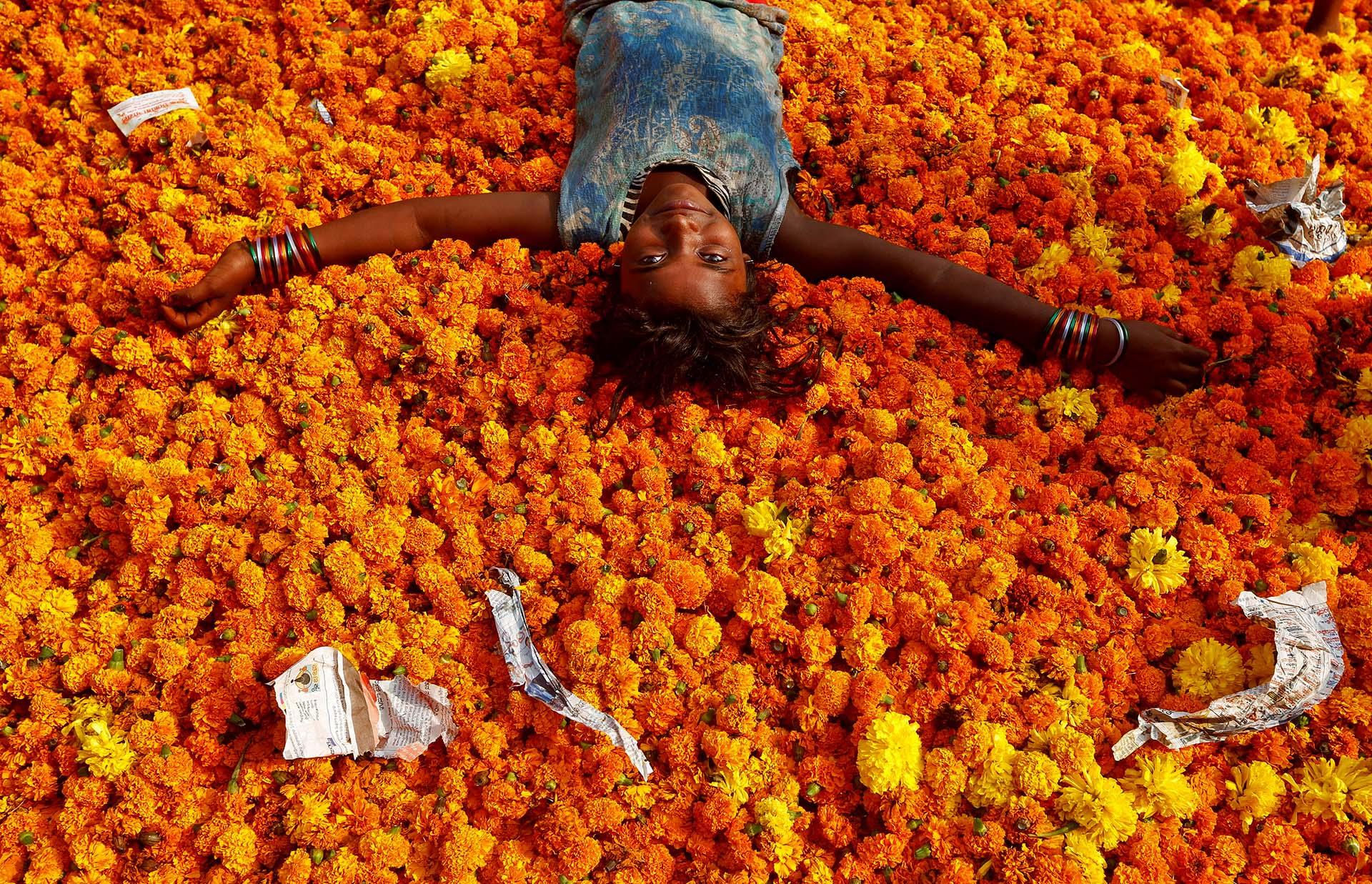 Una muchacha juega sobre flores desechadas fuera de un mercado, el día después de las celebraciones de Diwali en Mumbai