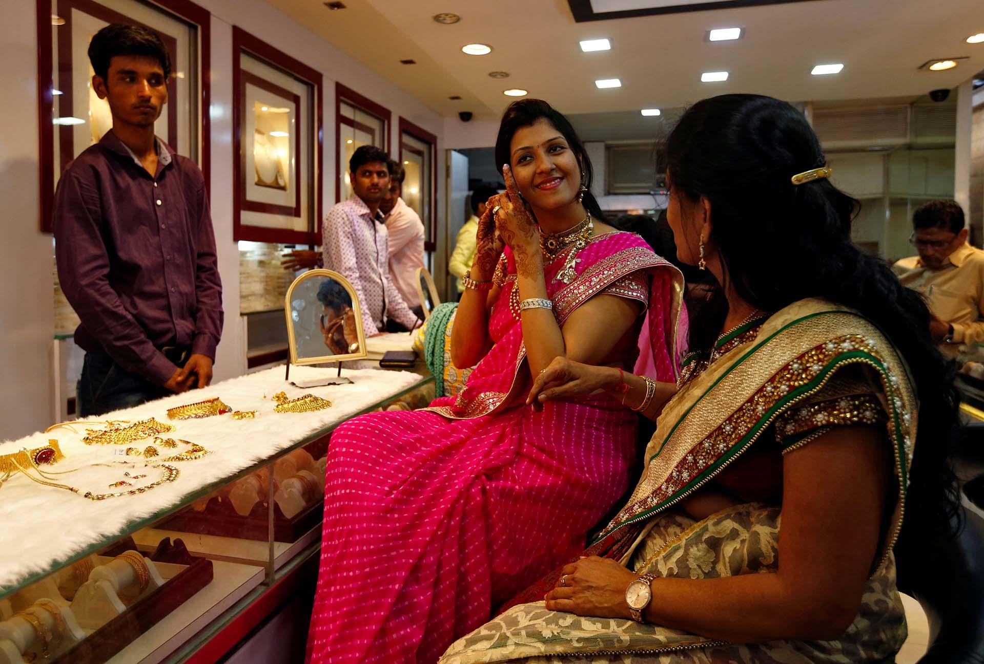 Una mujer se prueba un pendiente de oro en una joyería durante Dhanteras, un festival hindú asociado con Lakshmi, la diosa de la riqueza, en Mumbai