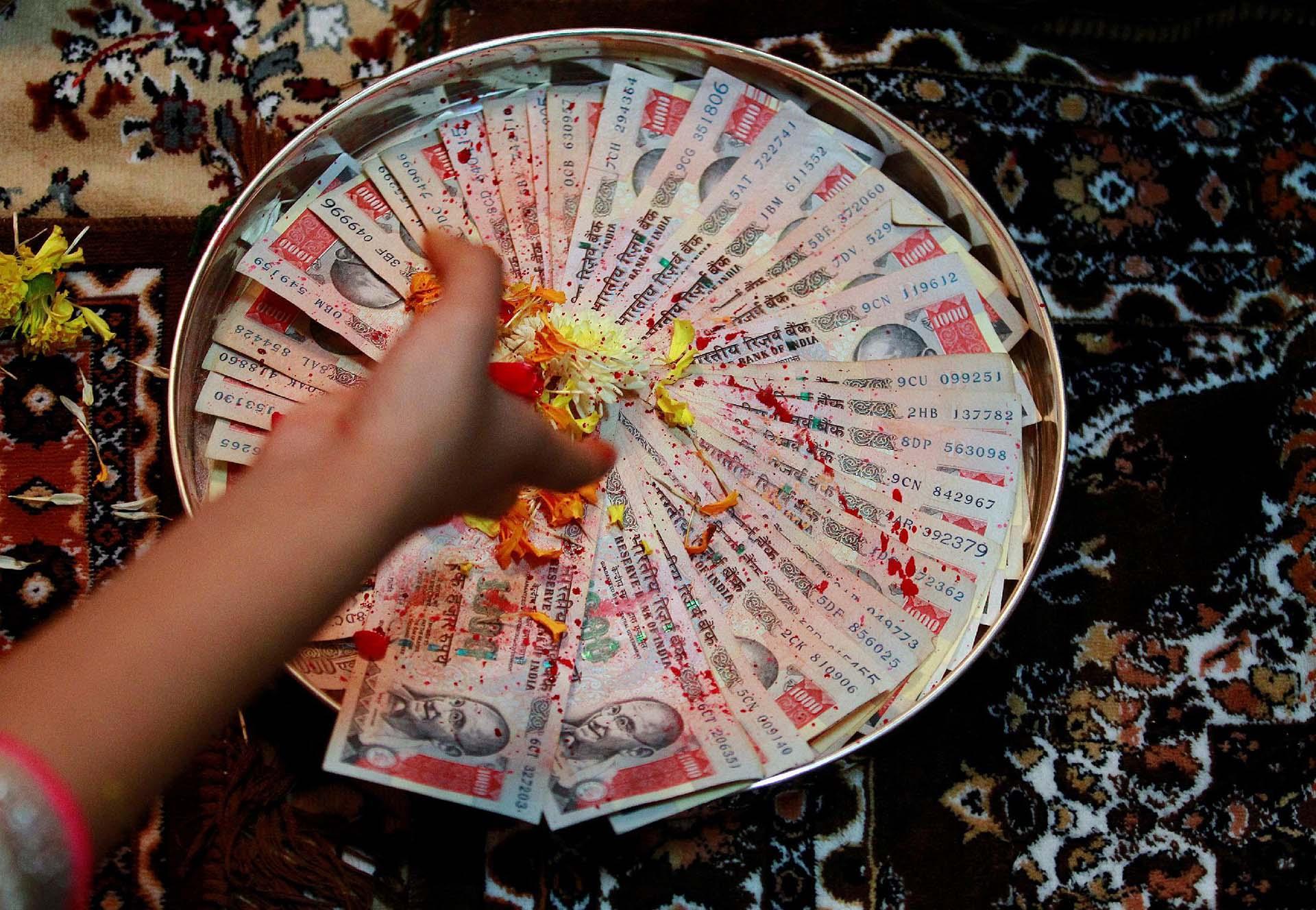 Una mujer coloca pétalos de flores sobre 1000 rupias indias, como parte de un ritual durante Dhanteras, un festival hindú asociado con Lakshmi, la diosa de la riqueza, en Ahmedabad