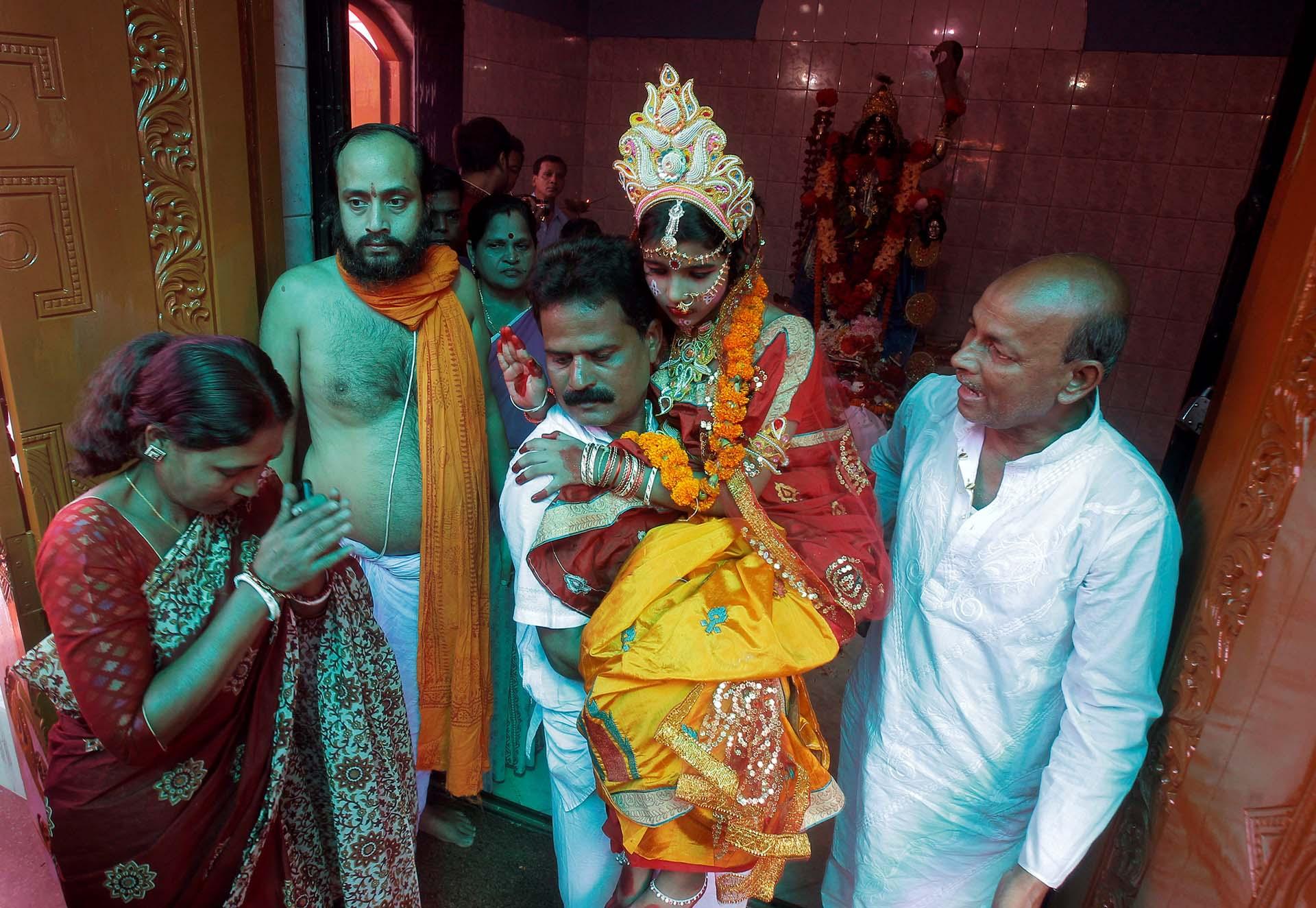 Un devoto hindú lleva a Susmita Bhattacharjee, una niña de nueve años vestida como Kumari, que es adorada durante el festival Kali Puja en Agartala