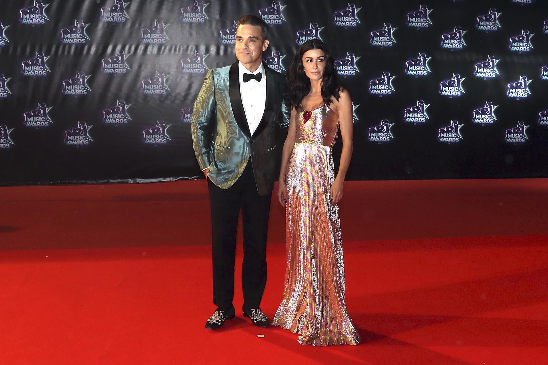 Con un smoking brilloso y zapatos bordados, Robbie Williams fue otra de las estrellas que desfiló por la red carpet y arribó en compañía de la cantante francesa, Jennifer