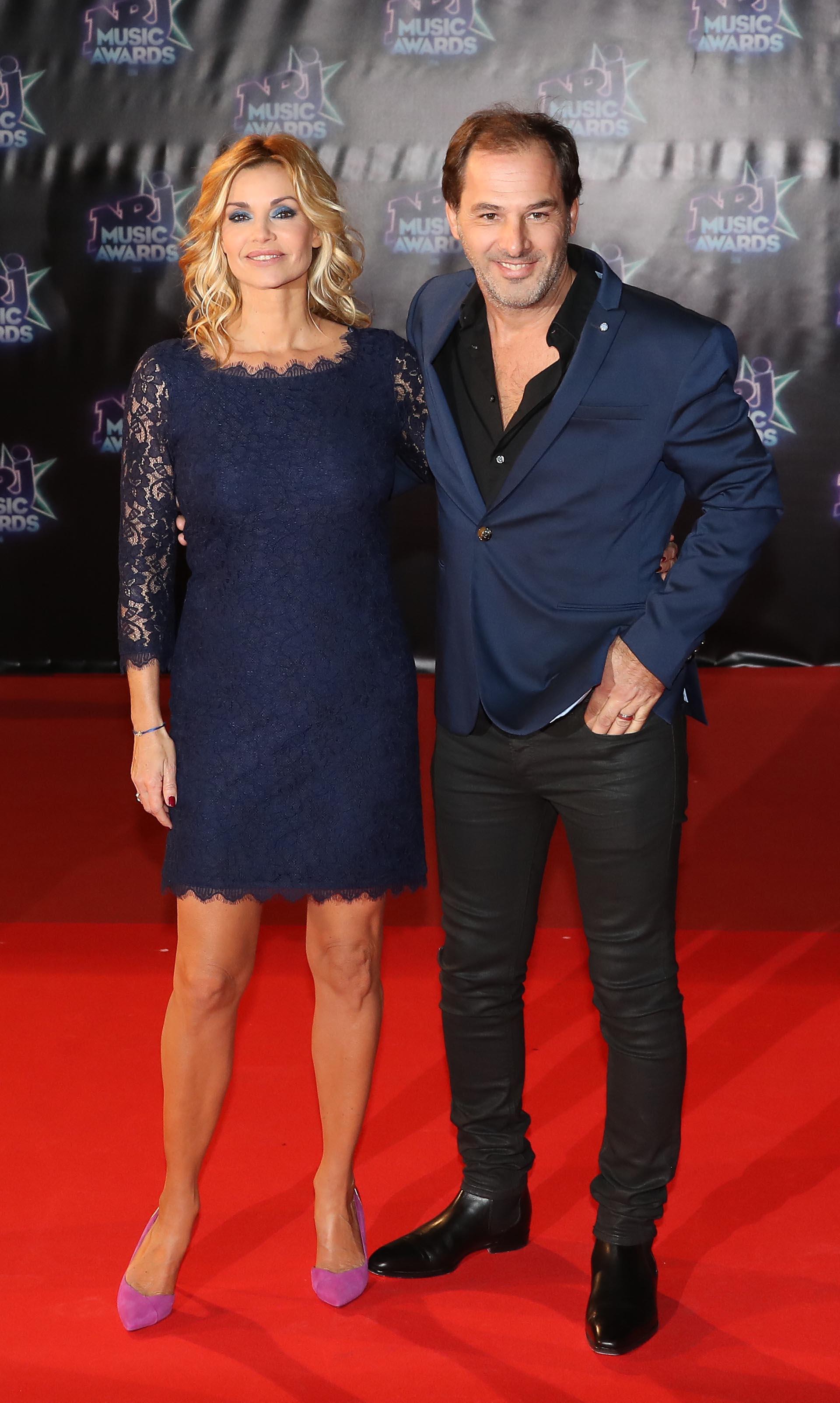 Ingrid Chauvin con un vestido de cóctel en encaje azul y stilettos lavanda, posa junto a su marido, Thierry Peythieu