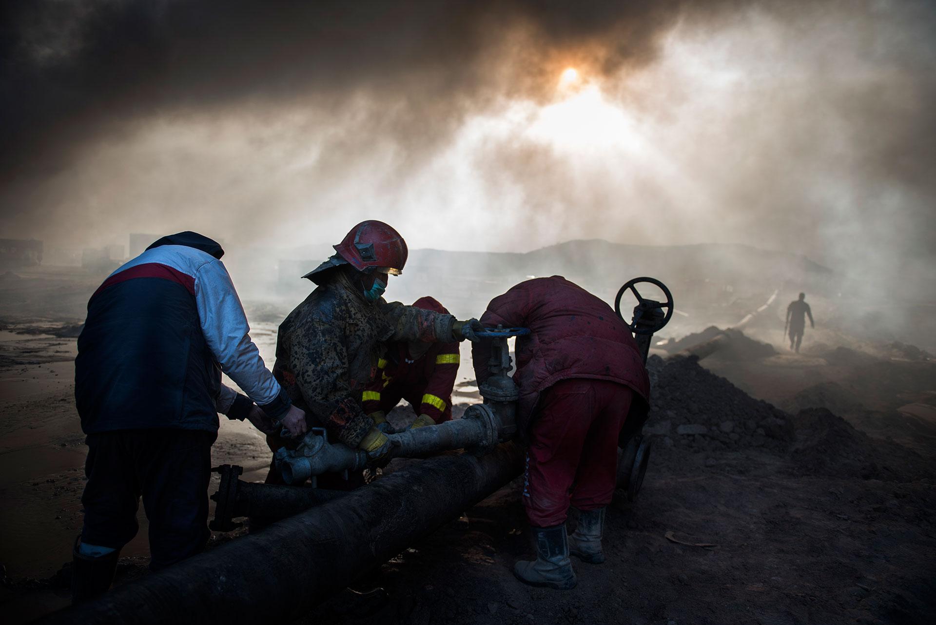 Los bomberos, con cascos rojos y máscaras, tratan de extinguir el fuego en los pozos de petroleo incendiados (AFP)