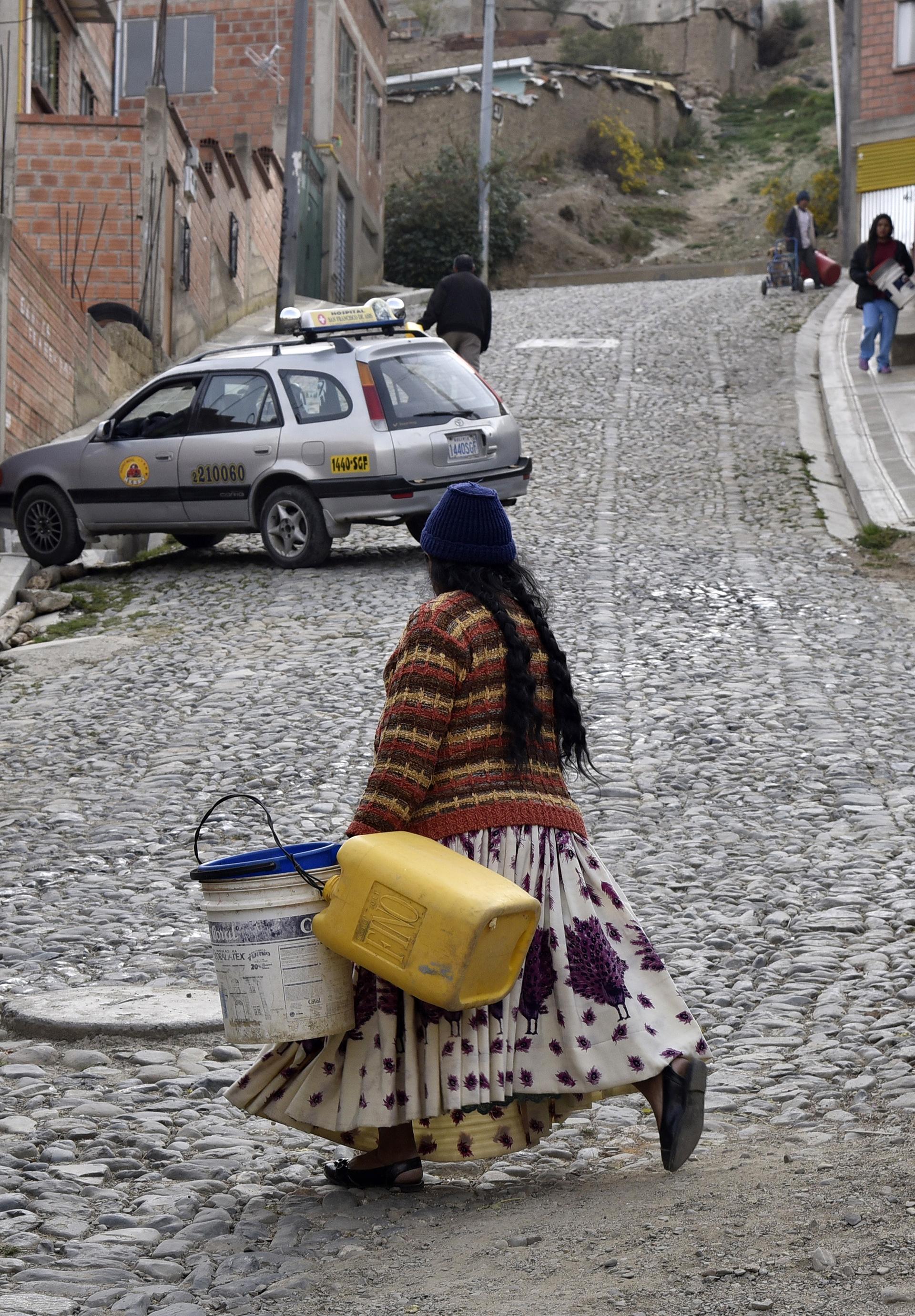 Una mujer camina por las calles de La Paz en busca de agua (AFP)